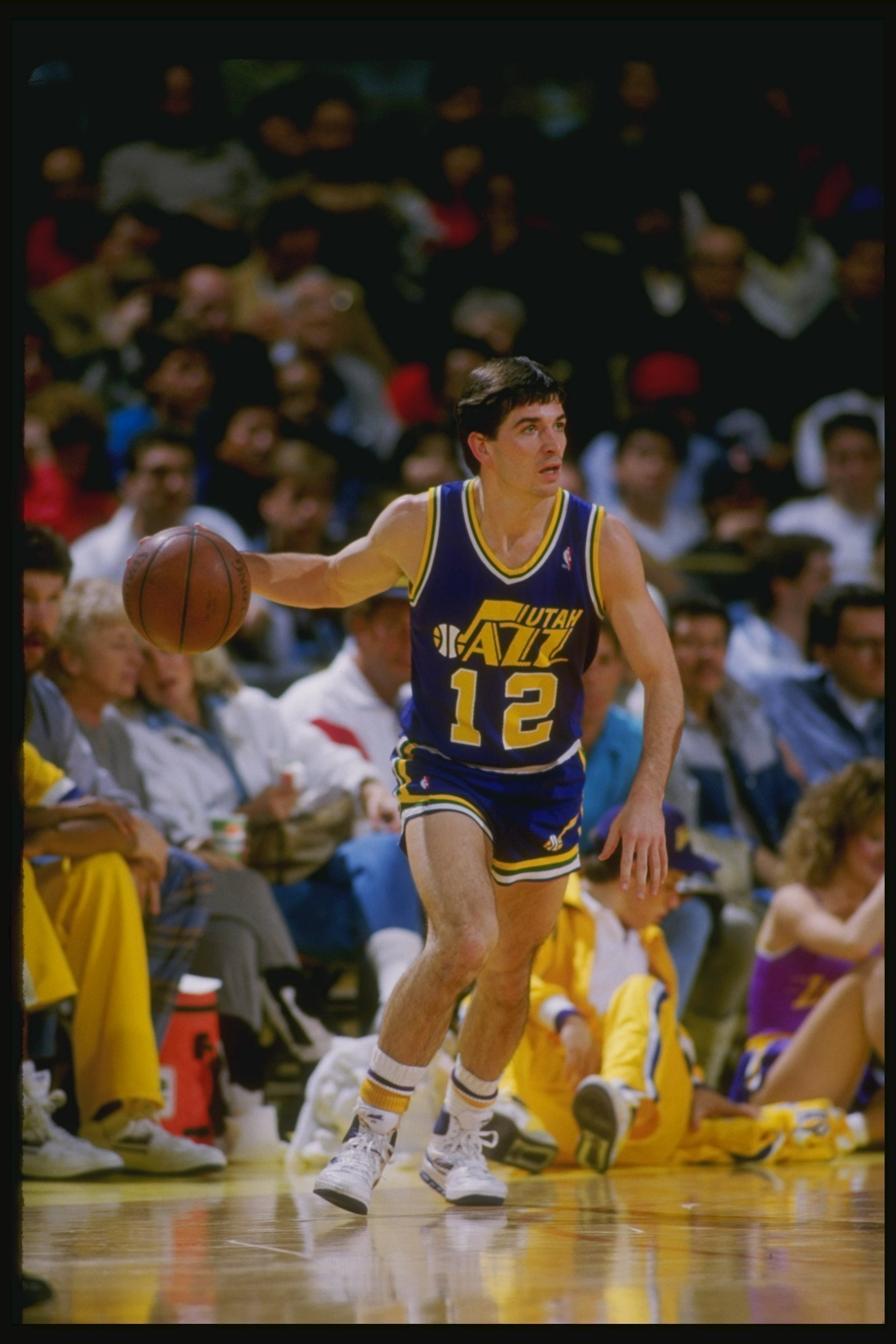 Guard John Stockton of the Utah Jazz dribbles the ball down the court during a game against the Los Angeles Lakers at the Great Western Forum in Inglewood, California.