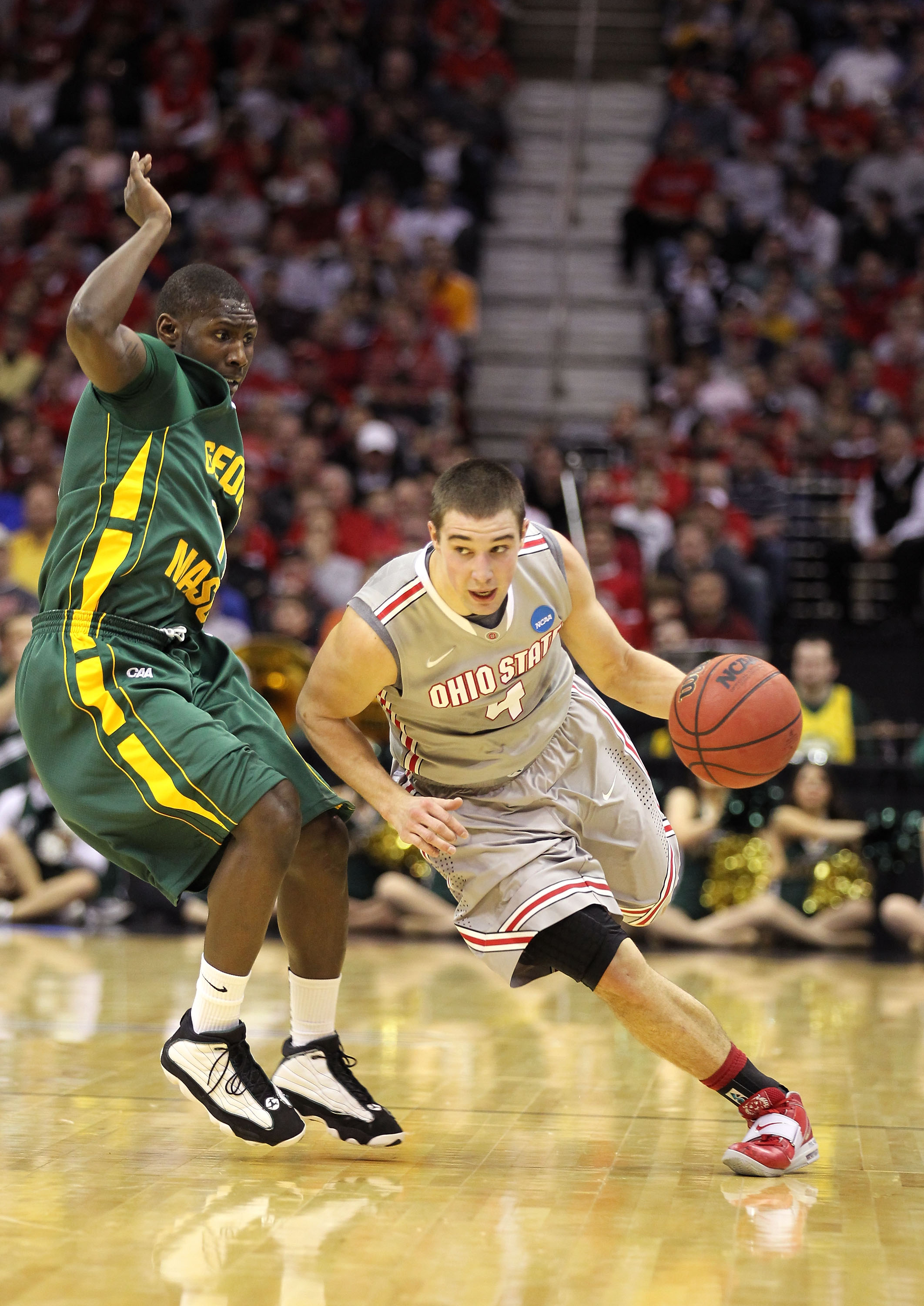 CLEVELAND, OH - MARCH 20: Aaron Craft #4 of the Ohio State Buckeyes dribbles around Vertrail Vaughns #11 of the George Mason Patriots during the third of the 2011 NCAA men's basketball tournament at Quicken Loans Arena on March 20, 2011 in Cleveland, Ohio