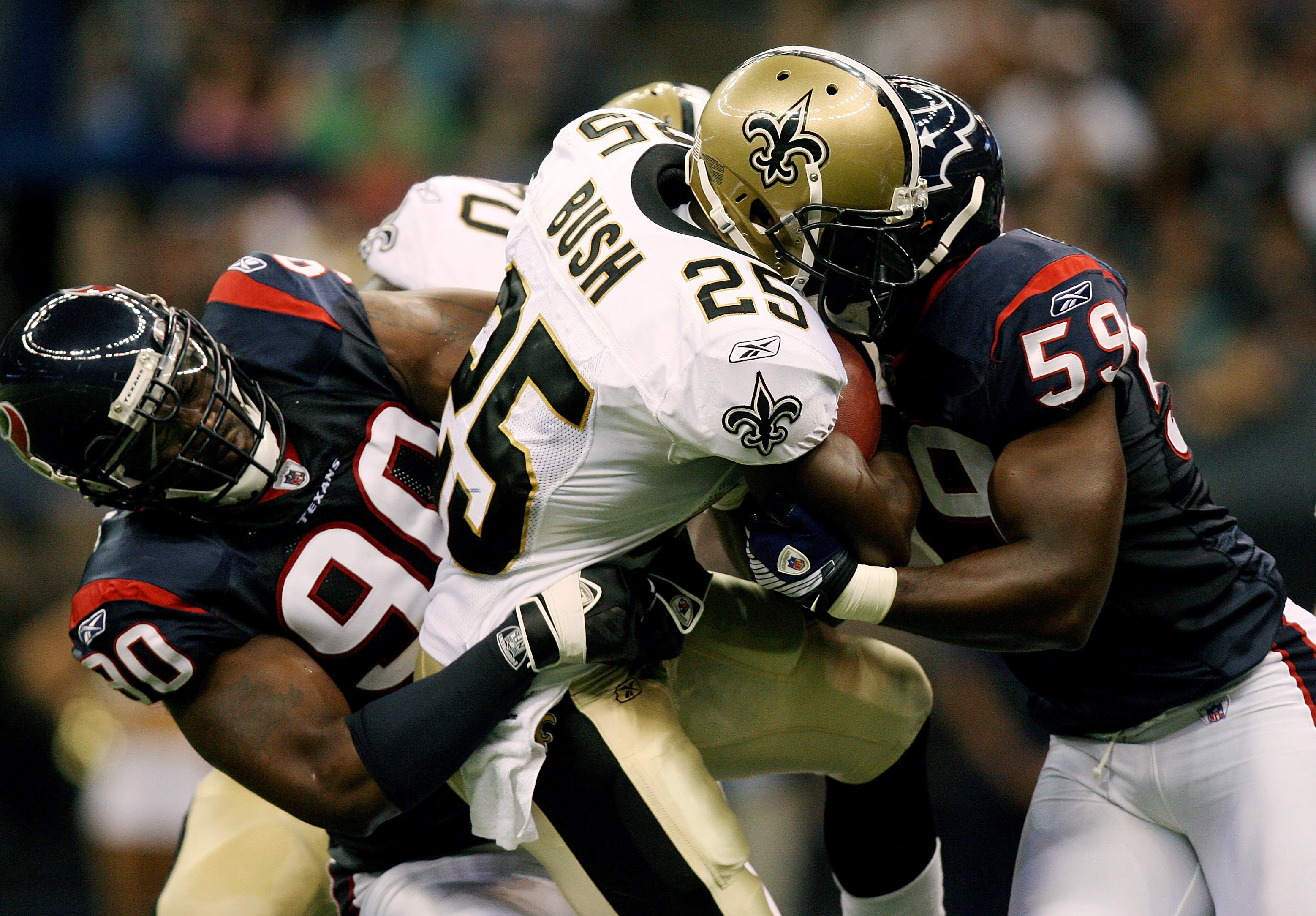 NEW ORLEANS - AUGUST 16:  Defensive end Mario Williams #90 and linebacker DeMeco Ryans #59 of the Houston Texans brings down running back Reggie Bush #25 of the New Orleans Saints during a pre-season game at Louisiana Superdome on August 16, 2008 in New O