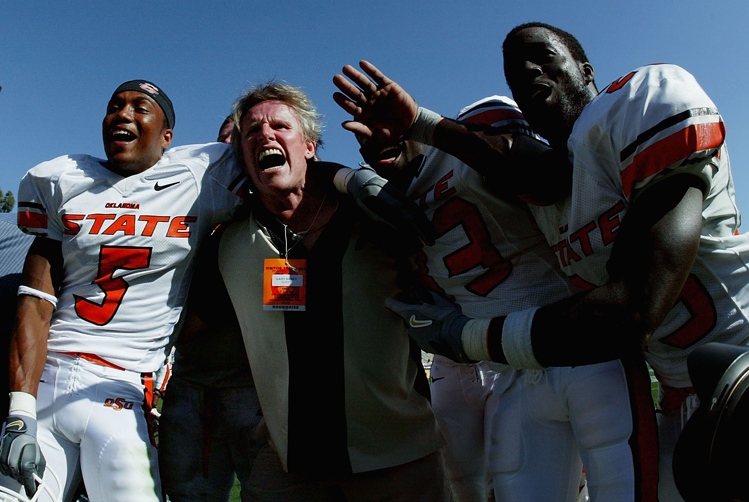 PASADENA, CA - SEPTEMBER 4:  Actor Gary Busey celebrates with victory with cornerback Ricky Coxeff #5 and wide receiver Chijuan Mack #83 of the Oklahoma State Cowboys and other teammates after defeating the UCLA Bruins on September 4, 2004 at the Rose Bow