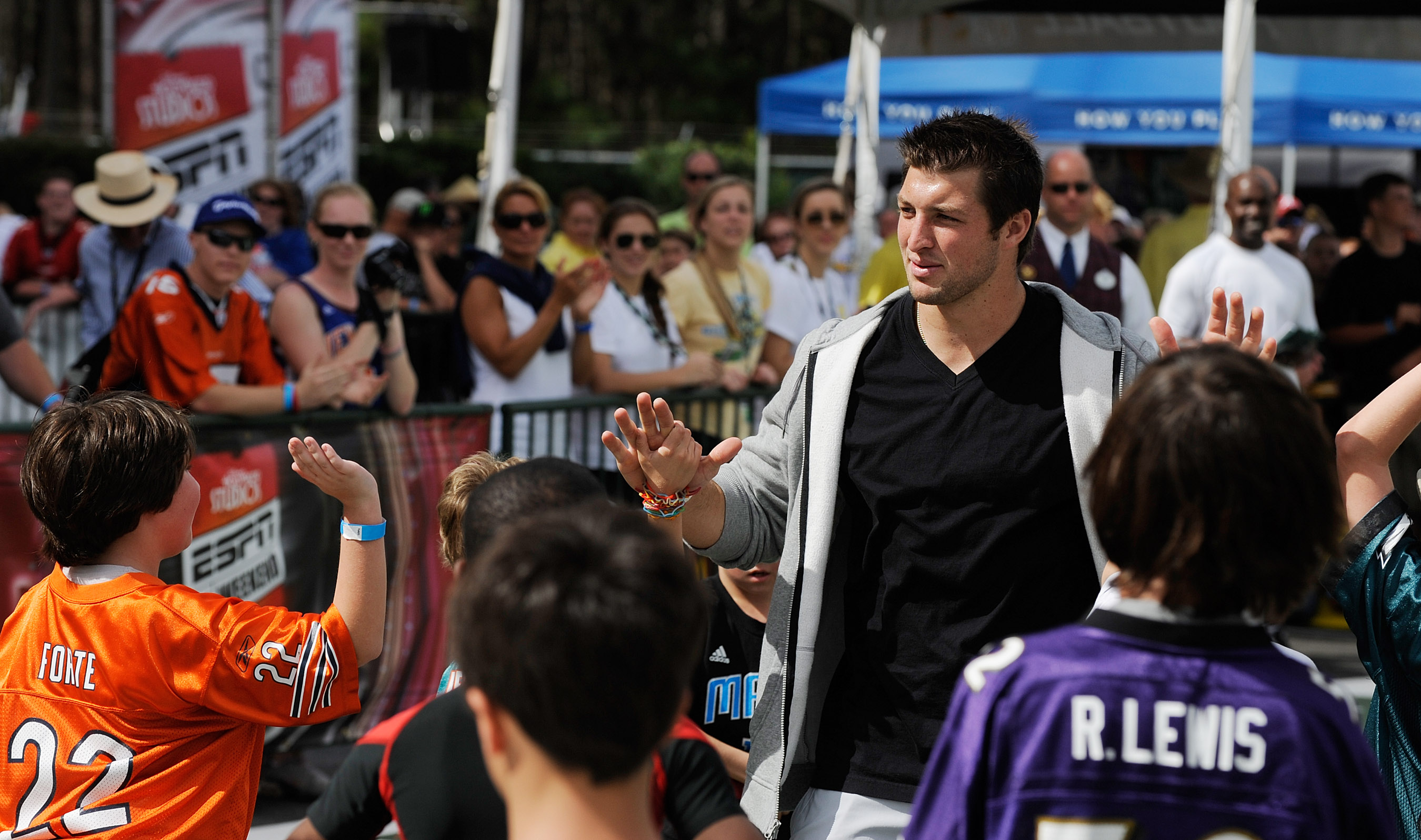 LAKE BUENA VISTA, FL - MARCH 05: In this handout photo provided by Disney Parks, Denver Broncos Quarterback Tim Tebow congratulates a group of young fans after a game of flag football at 'ESPN The Weekend' on March 05, 2011 at Disney's Hollywood Studios P