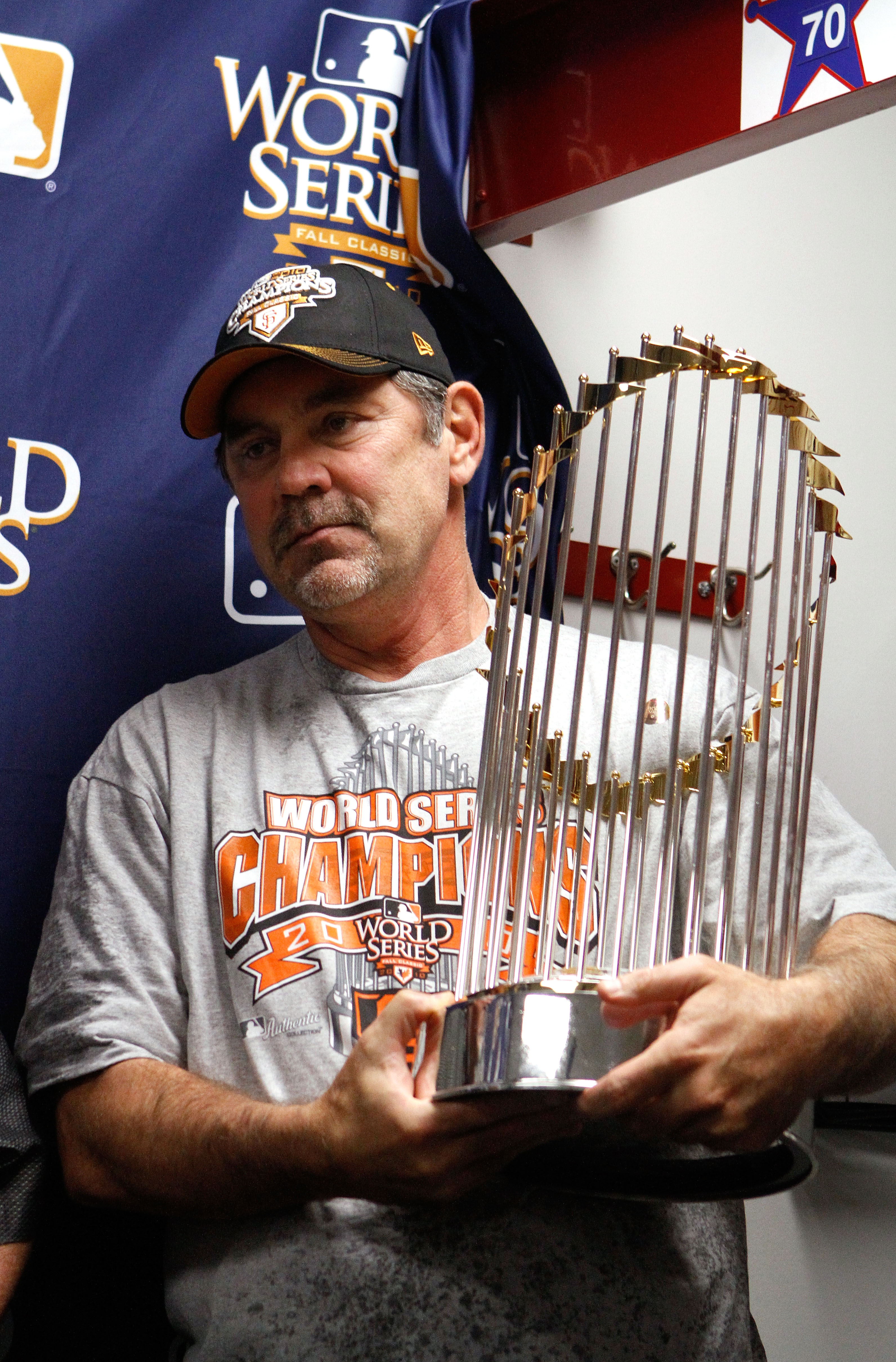 ARLINGTON, TX - NOVEMBER 01:  Manager Bruce Bochy of the San Francisco Giants celebrates with the World Series trophy in the locker room after the Giants won 3-1 against the Texas Rangers in Game Five of the 2010 MLB World Series at Rangers Ballpark in Ar