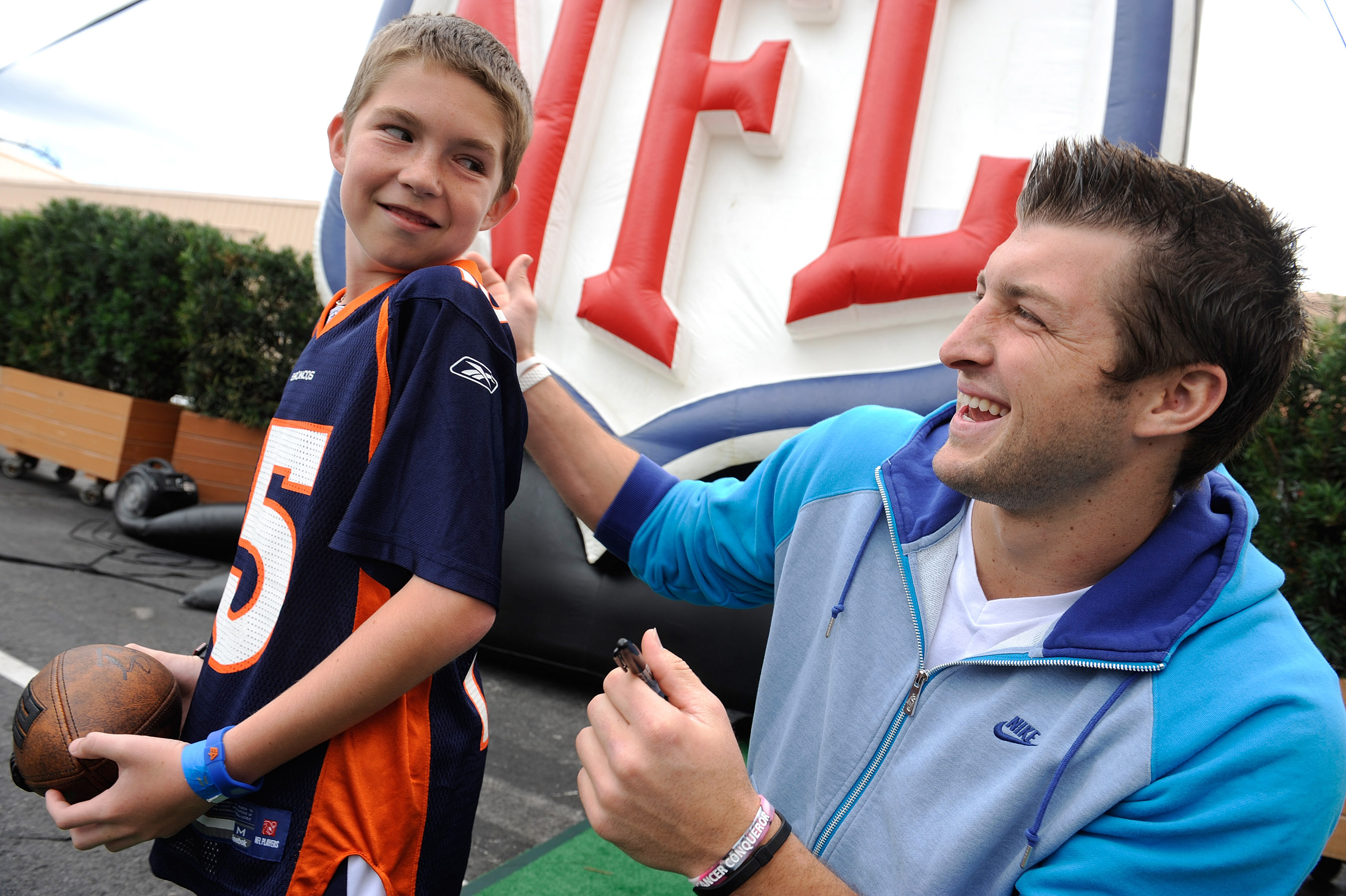 LAKE BUENA VISTA, FL - MAR 04: In this handout image provided by Disney Parks,  Denver Broncos quarterback Tim Tebow autographs a jersey for Cole Hoover, age 11, from Cape Coral, Florida at Disney's Hollywood Studios park in Lake Buena Vista, Florida on M