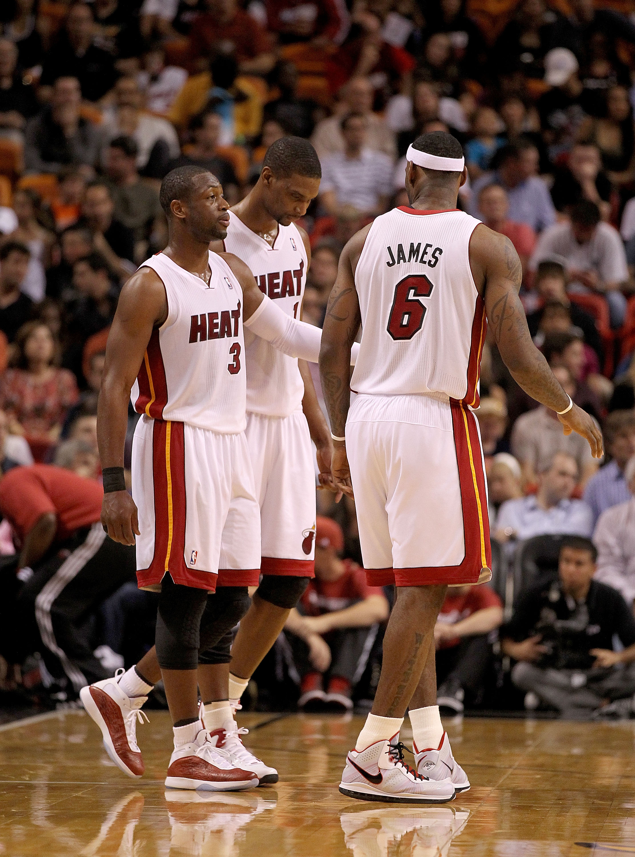 MIAMI, FL - FEBRUARY 25:  LeBron James #6, Dwyane Wade #3 and Chris Bosh #1 of the Miami Heat talk during a game against the Washington Wizards at American Airlines Arena on February 25, 2011 in Miami, Florida. NOTE TO USER: User expressly acknowledges an