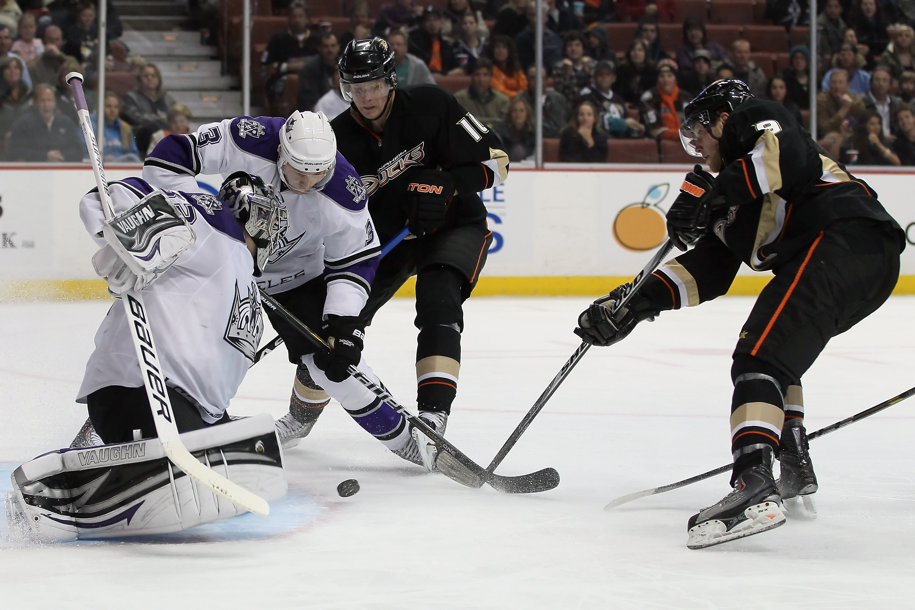 ANAHEIM, CA - NOVEMBER 29:  (L-R) Goaltender Jonathan Quick #32 of the Los Angeles Kings makes a save, as teammate Jack Johnson #3 defends the puck from Corey Perry #10 and Bobby Ryan #9 of the Anaheim Ducks during the third period at the Honda Center on
