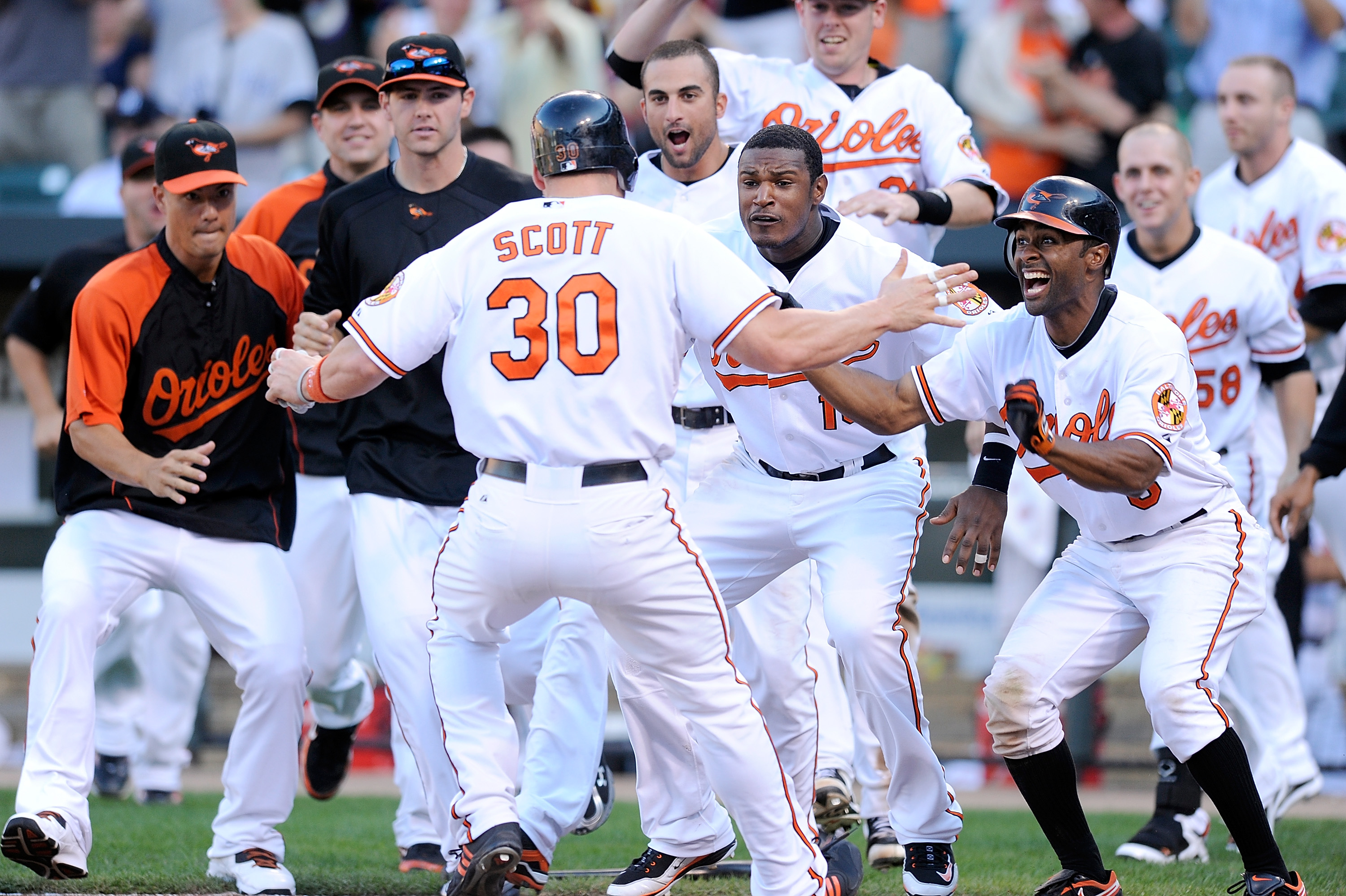 BALTIMORE - SEPTEMBER 19:  Luke Scott #30 of the Baltimore Orioles is congratulated by Adam Jones #10, Corey Patterson #6, Nick Markakis #21 and other teammates after scoring the game winning run in the eleventh inning against the New York Yankees at Camd