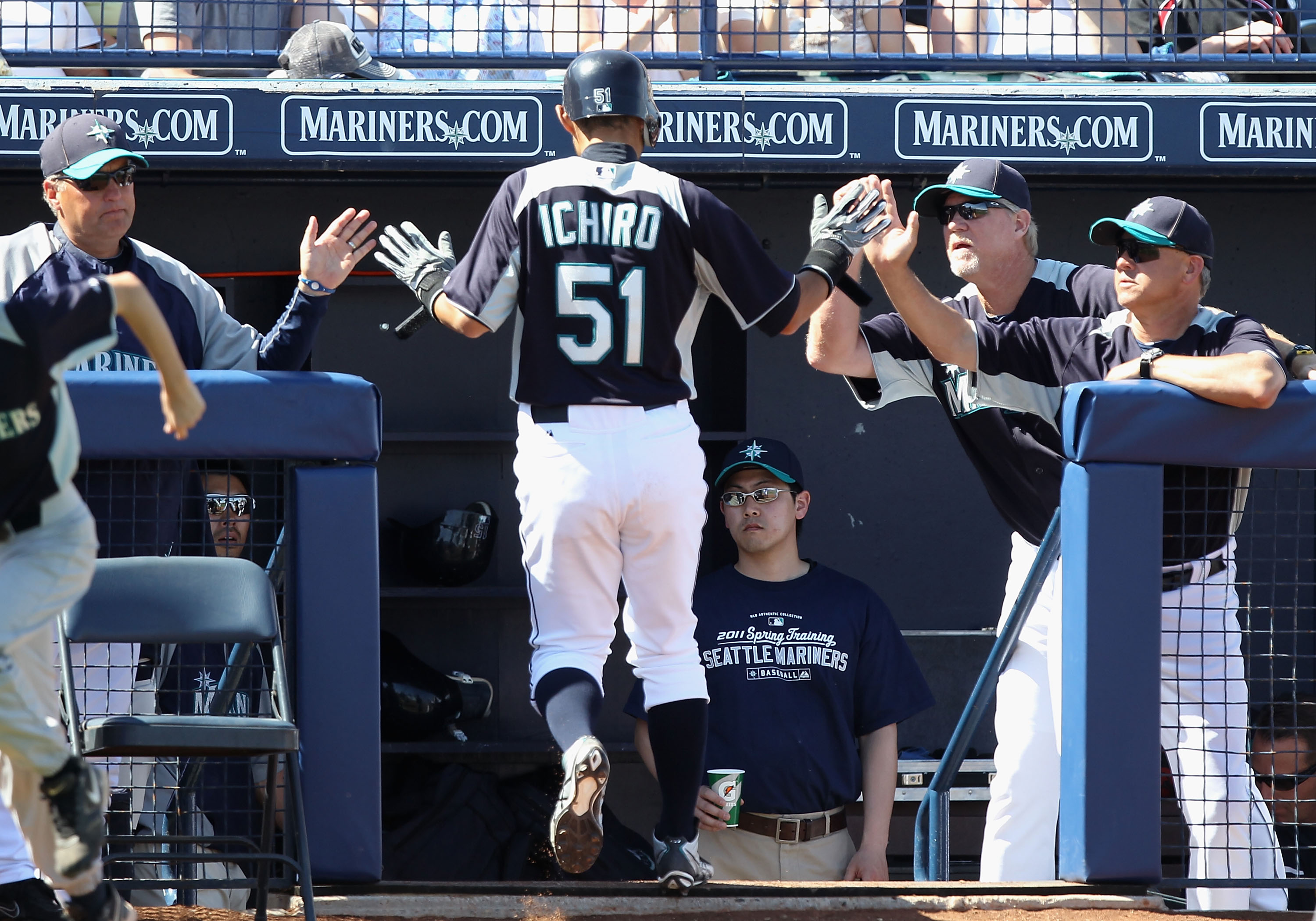 PEORIA, AZ - MARCH 12:  Ichiro Suzuki #51 of the Seattle Mariners high fives teammates after scoring a run against the Oakland Athletics during the second inning of the spring training game at Peoria Stadium on March 12, 2011 in Peoria, Arizona.  (Photo b