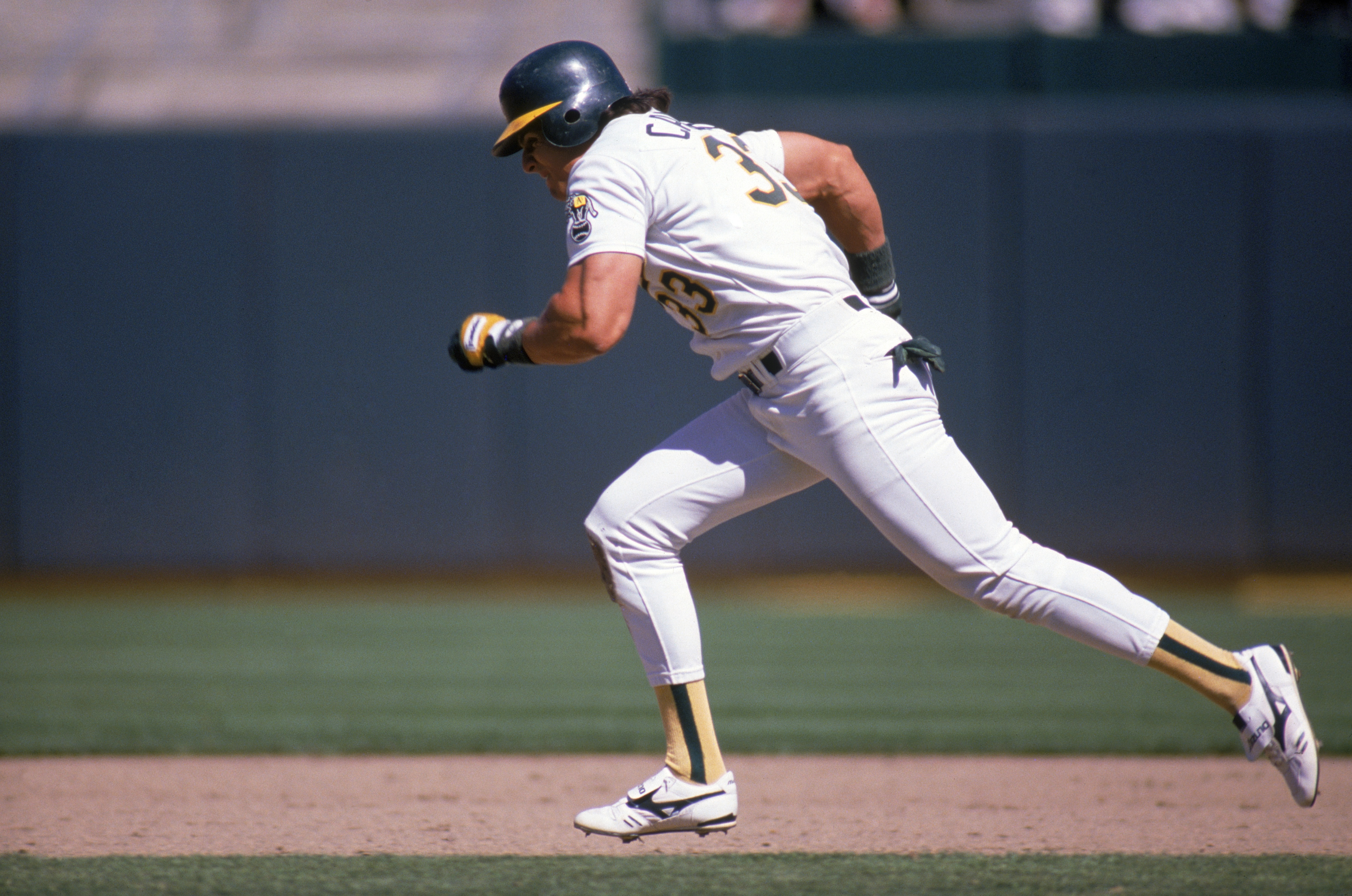 OAKLAND, CA -1988:  Jose Canseco #33 of the Oakland Athletics runs between the bases during a 1988 MLB season game at Oakland-Alameda County Coliseum in Oakland, California.  (Photo by Otto Greule Jr/Getty Images)
