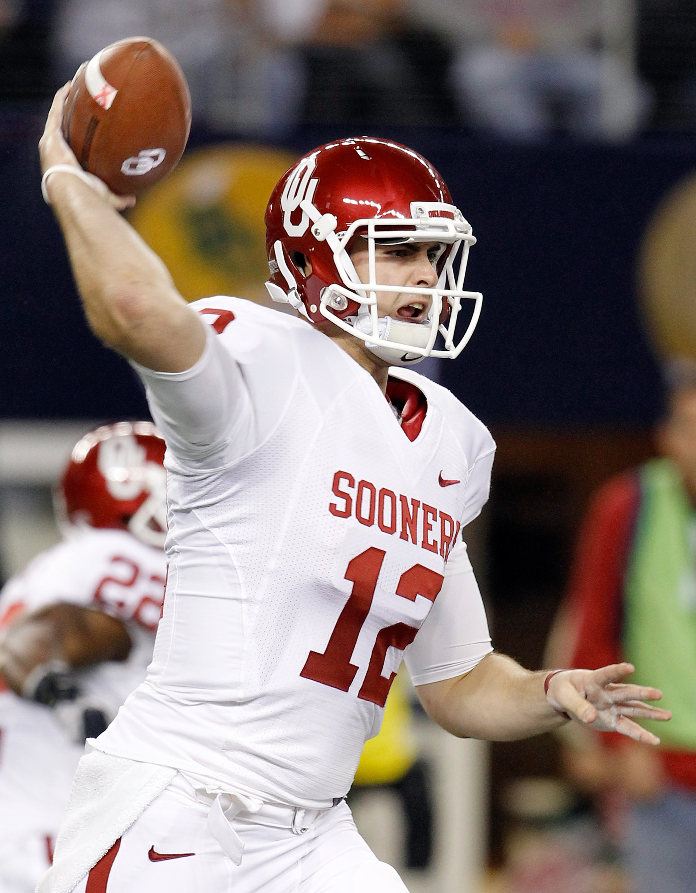 ARLINGTON, TX - DECEMBER 04:  Quarterback Landry Jones #12 of the Oklahoma Sooners looks for an open receiver against the Nebraska Cornhuskers at Cowboys Stadium on December 4, 2010 in Arlington, Texas.  The Sooners beat the Cornhuskers 23-20.  (Photo by