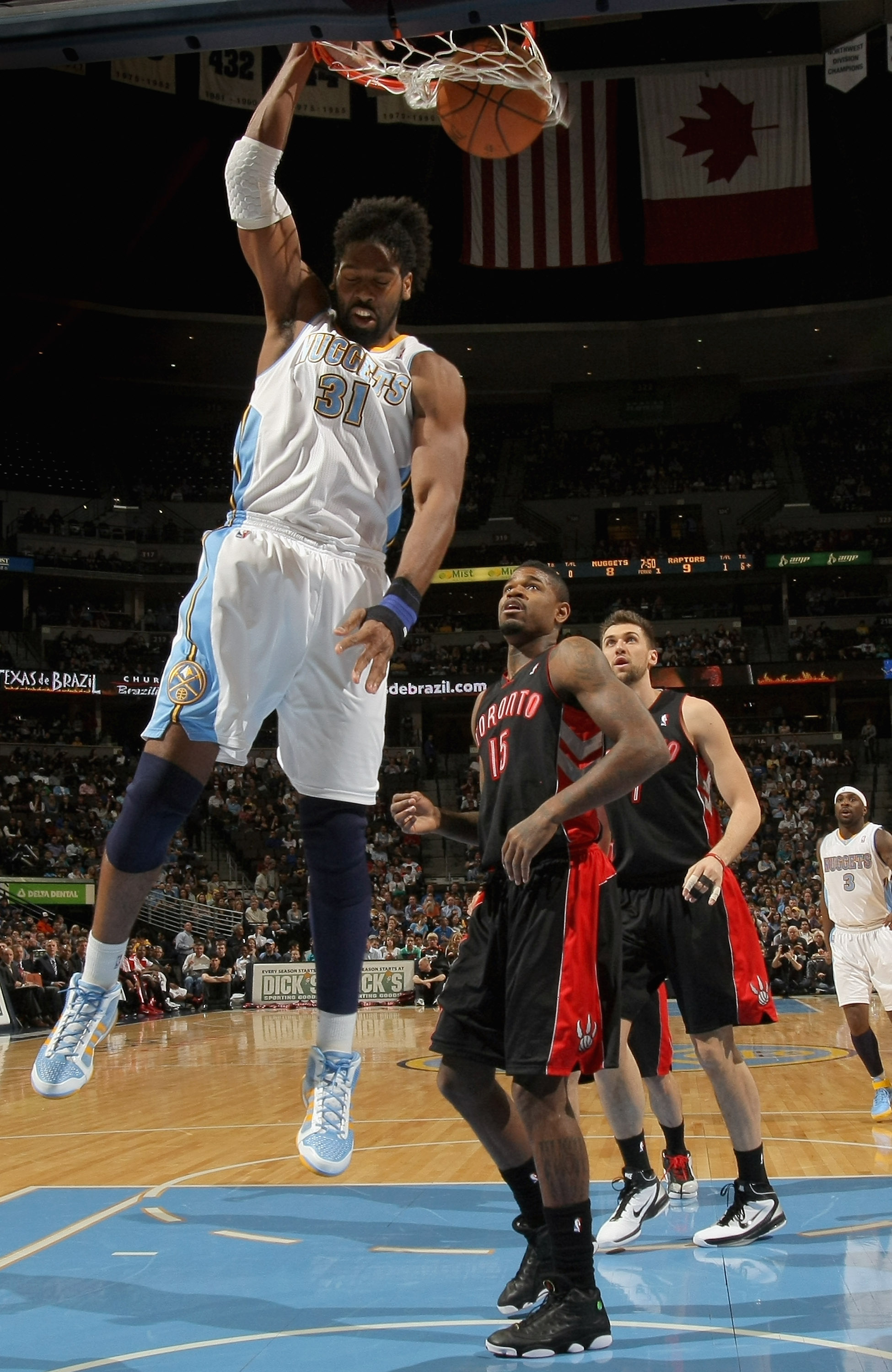 DENVER, CO - MARCH 21:  Nene #31 of the Denver Nuggets dunks the ball in front of Amir Johnson #15 of the Toronto Raptors at the Pepsi Center on March 21, 2011 in Denver, Colorado. NOTE TO USER: User expressly acknowledges and agrees that, by downloading