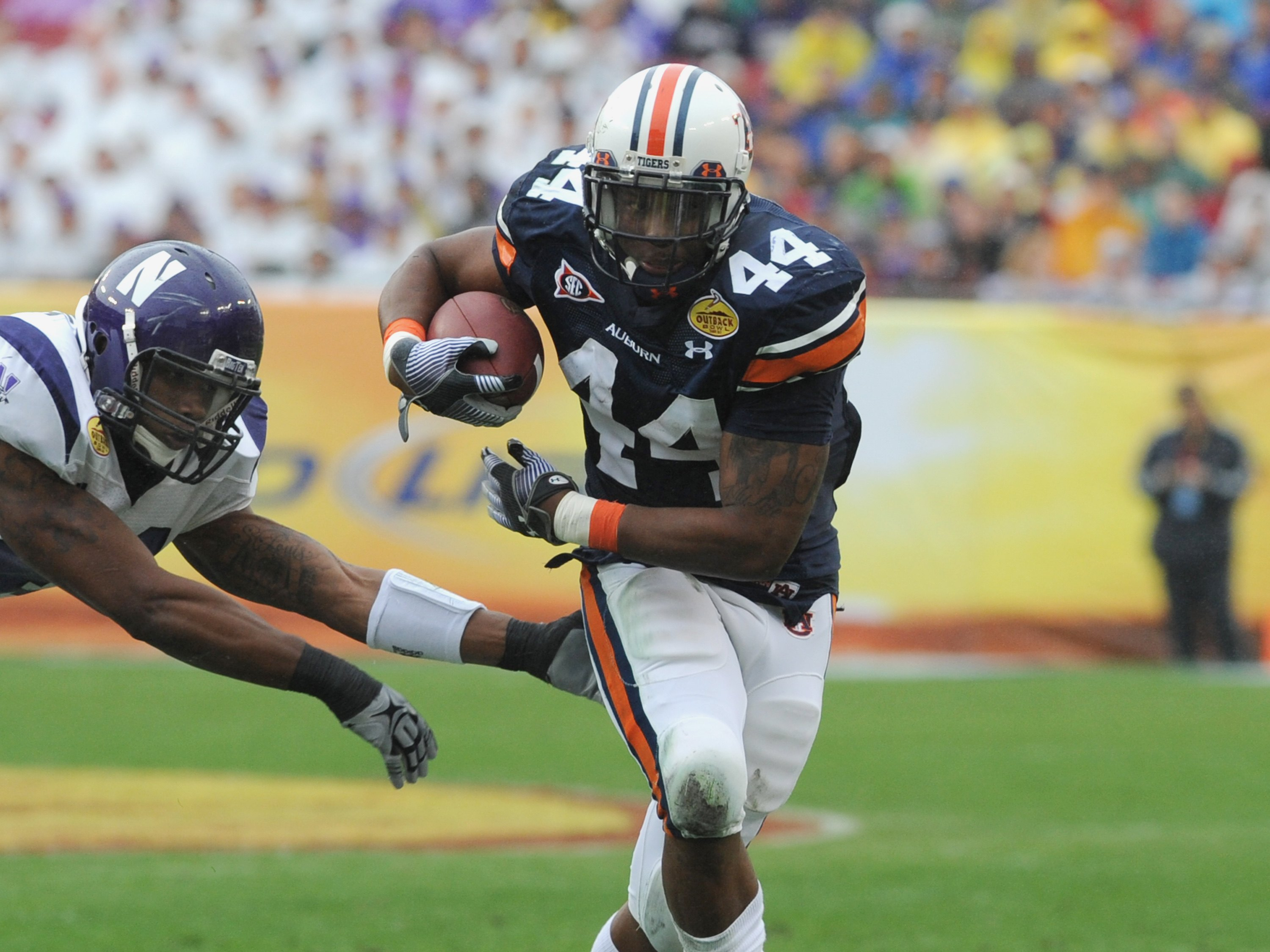 TAMPA, FL - JANUARY 1: Running back Ben Tate #44 of the Auburn Tigers rushes upfield against the Northwestern Wildcats in the Outback Bowl January 1, 2010 at Raymond James Stadium in Tampa, Florida.  (Photo by Al Messerschmidt/Getty Images)