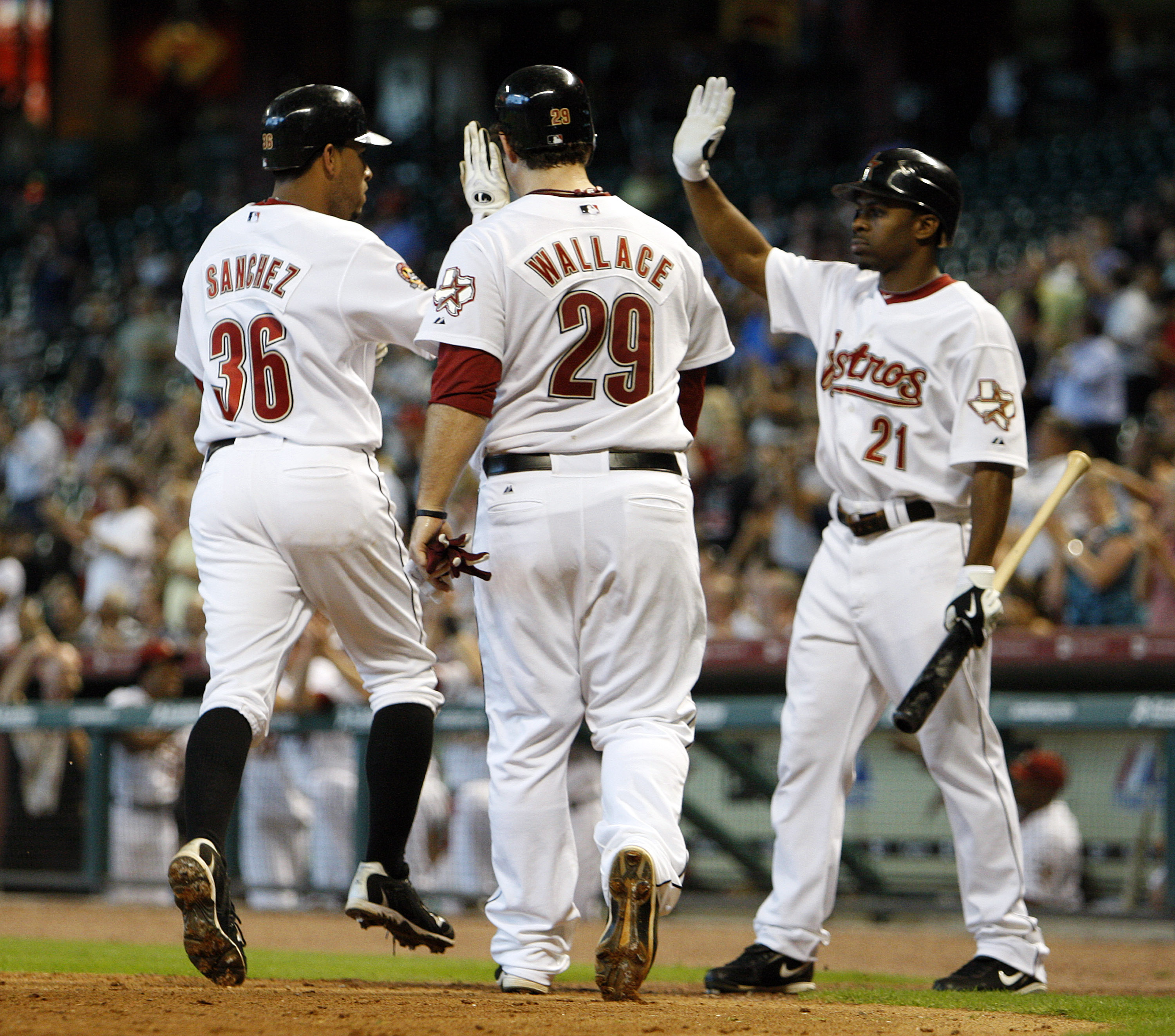 HOUSTON - SEPTEMBER 15:  Angel Sanchez #36 and Brett Wallace #29 of the Houston Astros score on a single by Brian Bogusevic of the Houston Astros in the fifth inning as Micahael Bourn greets  them at home plate during a baseball game against the Milwaukee