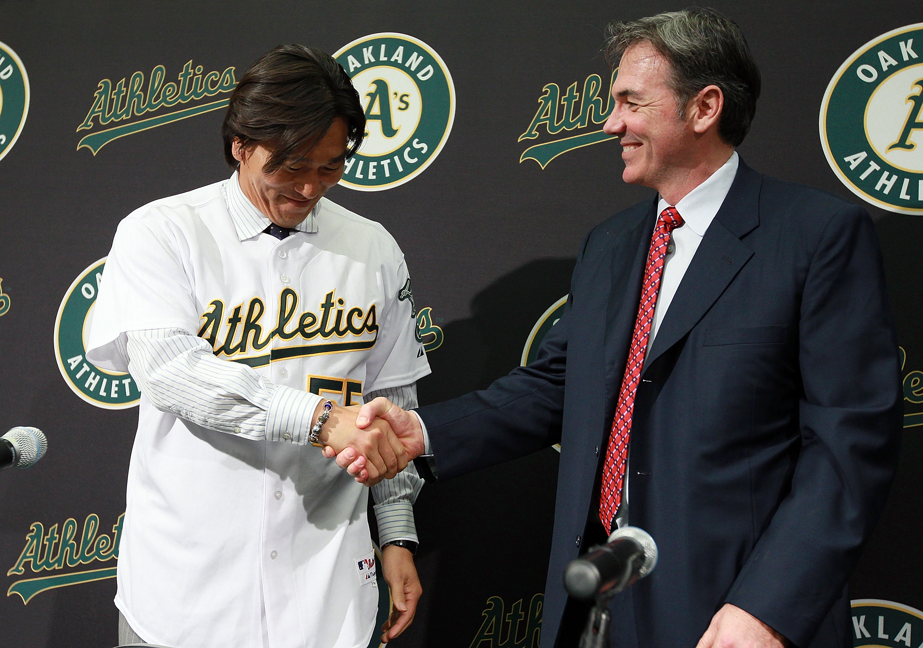 OAKLAND, CA - DECEMBER 14:  Hideki Matsui (L) shakes hands with Oakland Athletics general manager Billy Beane (R) after trying on his new jersey during a press conference where he was introduced as the newest member of the Oakland Athletics at Oakland-Ala