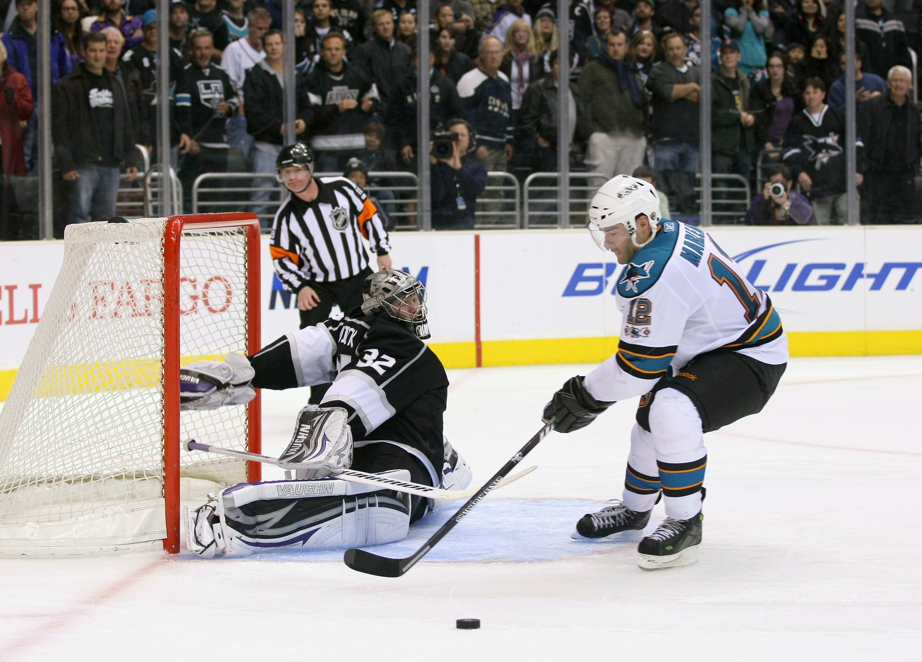 LOS ANGELES, CA - MARCH 24:  Goaltender Jonathan Quick #32 of the Los Angeles Kings slides out his right leg pad to defend the shot as Patrick Marleau #12 of the San Jose Sharks loses control of the puck during his shootout attempt in the NHL game at Stap