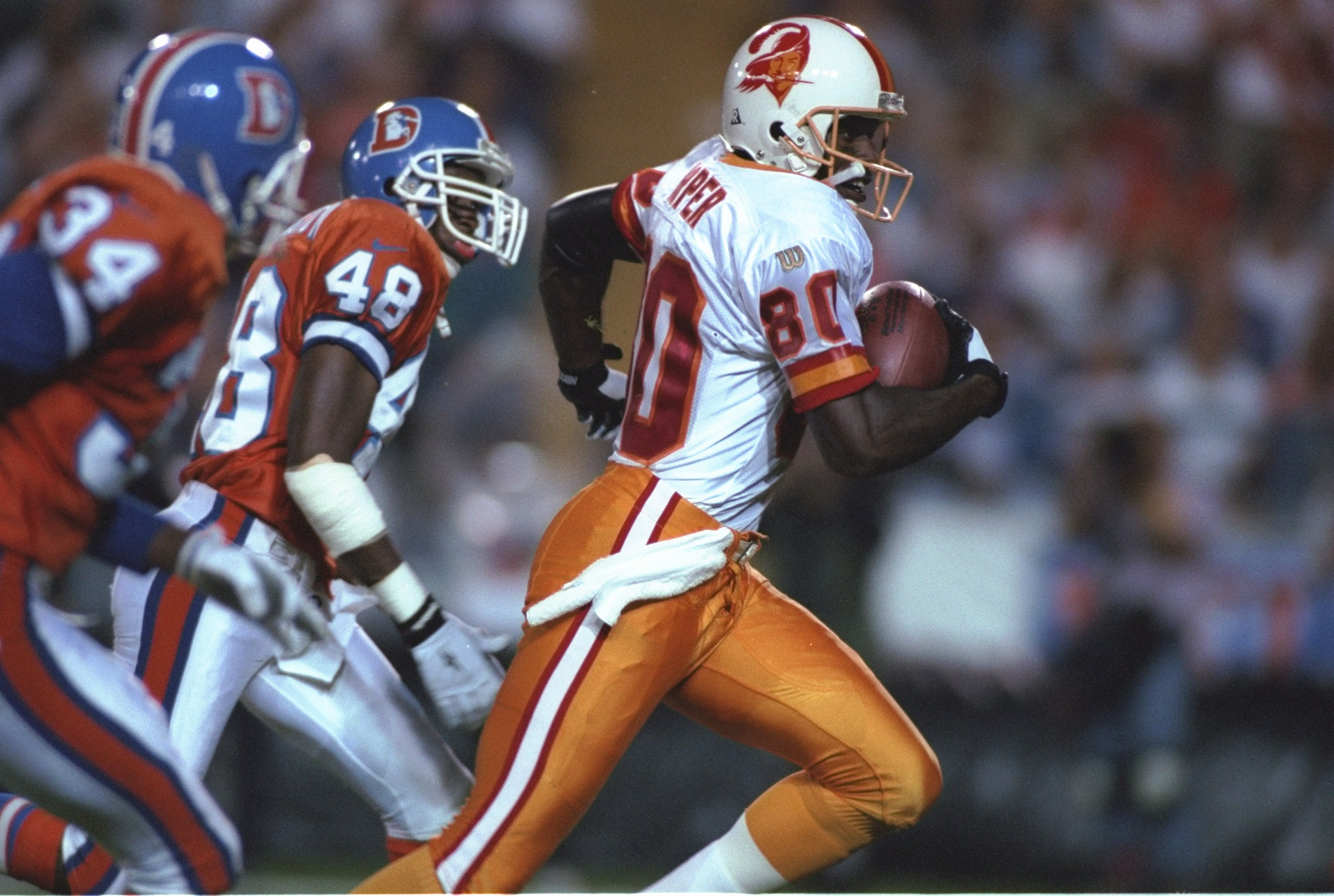 15 Sep 1996: Wide receiver Alvin Harper #80 of the Tampa Bay Buccaneers looks up field as he runs with the football while being pursued by defensive backs Lionel Washington #48 and Tyrone Braxton #34 of the Denver Broncos following a down field reception