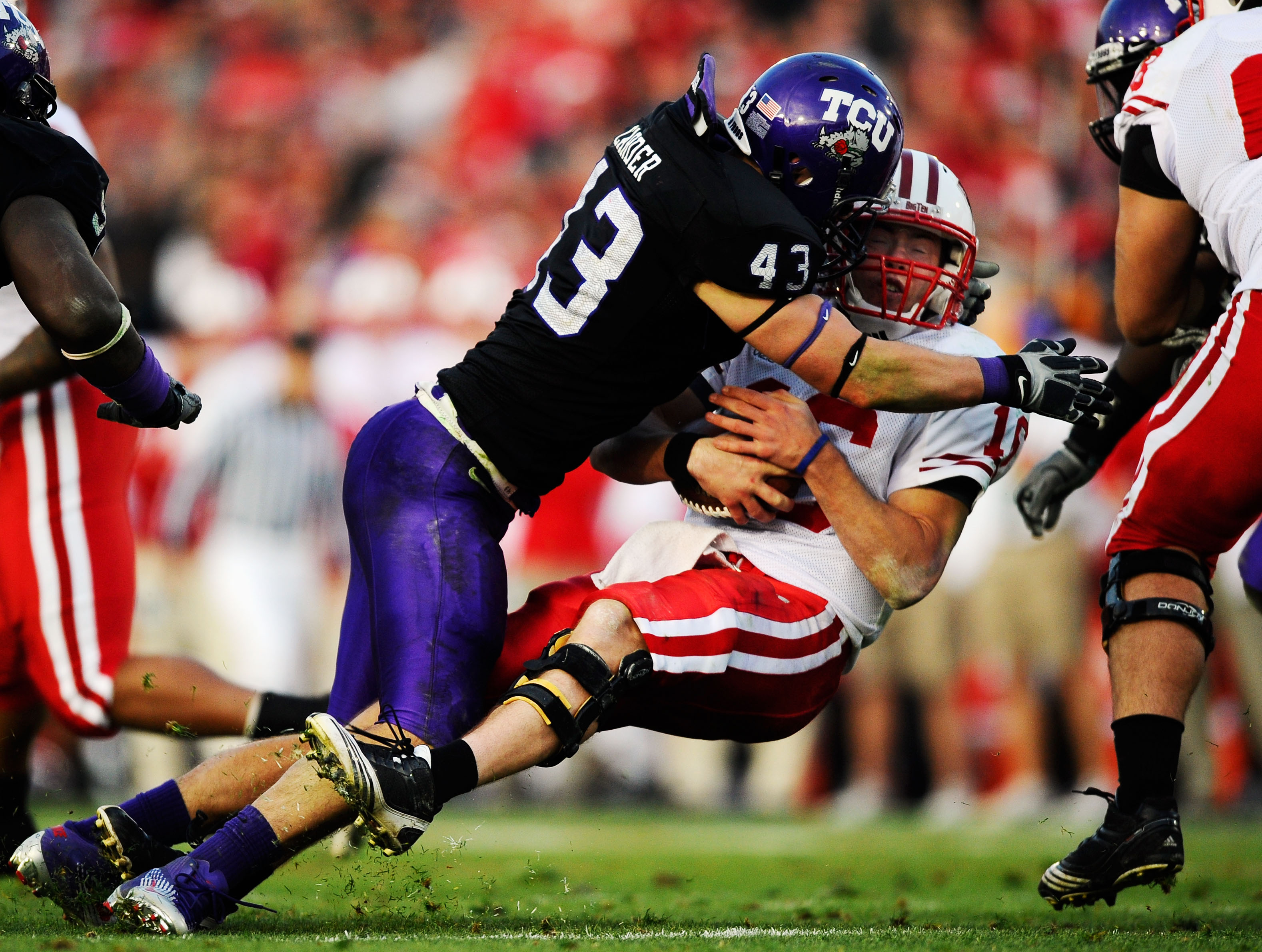 PASADENA, CA - JANUARY 01:  Quarterback Scott Tolzien #16 of the Wisconsin Badgers is sacked by linebacker Tank Carder #43 of the TCU Horned Frogs during the 97th Rose Bowl game on January 1, 2011 in Pasadena, California.  (Photo by Kevork Djansezian/Gett