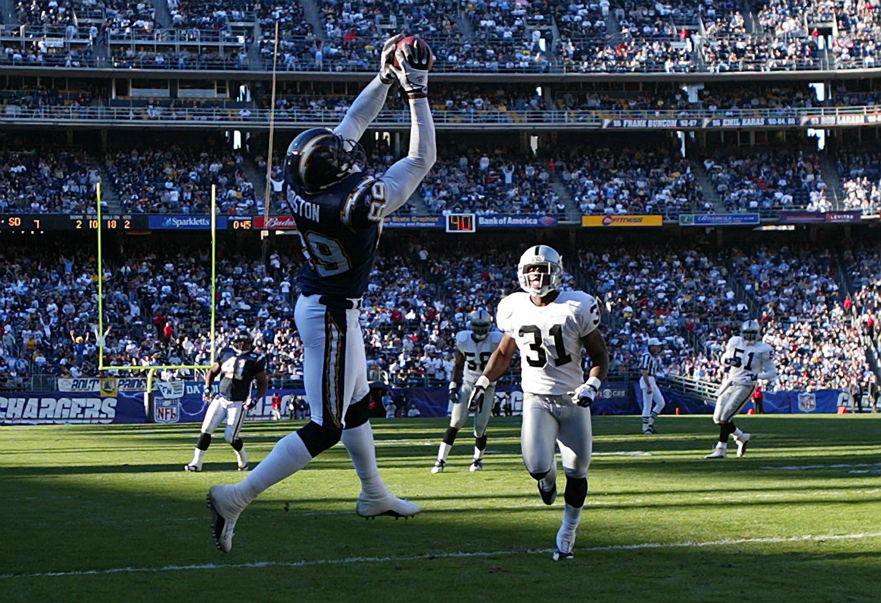 SAN DIEGO - DECEMBER 28: Wide Reciever David Boston #89 of the San Diego Chargers hauls in a touchdown pass as Phillip Buchanon #31 of the Oakland Raiders looks on in the 1st half  during their NFL  game on December 28, 2003 at Qualcomm Stadium in San Die