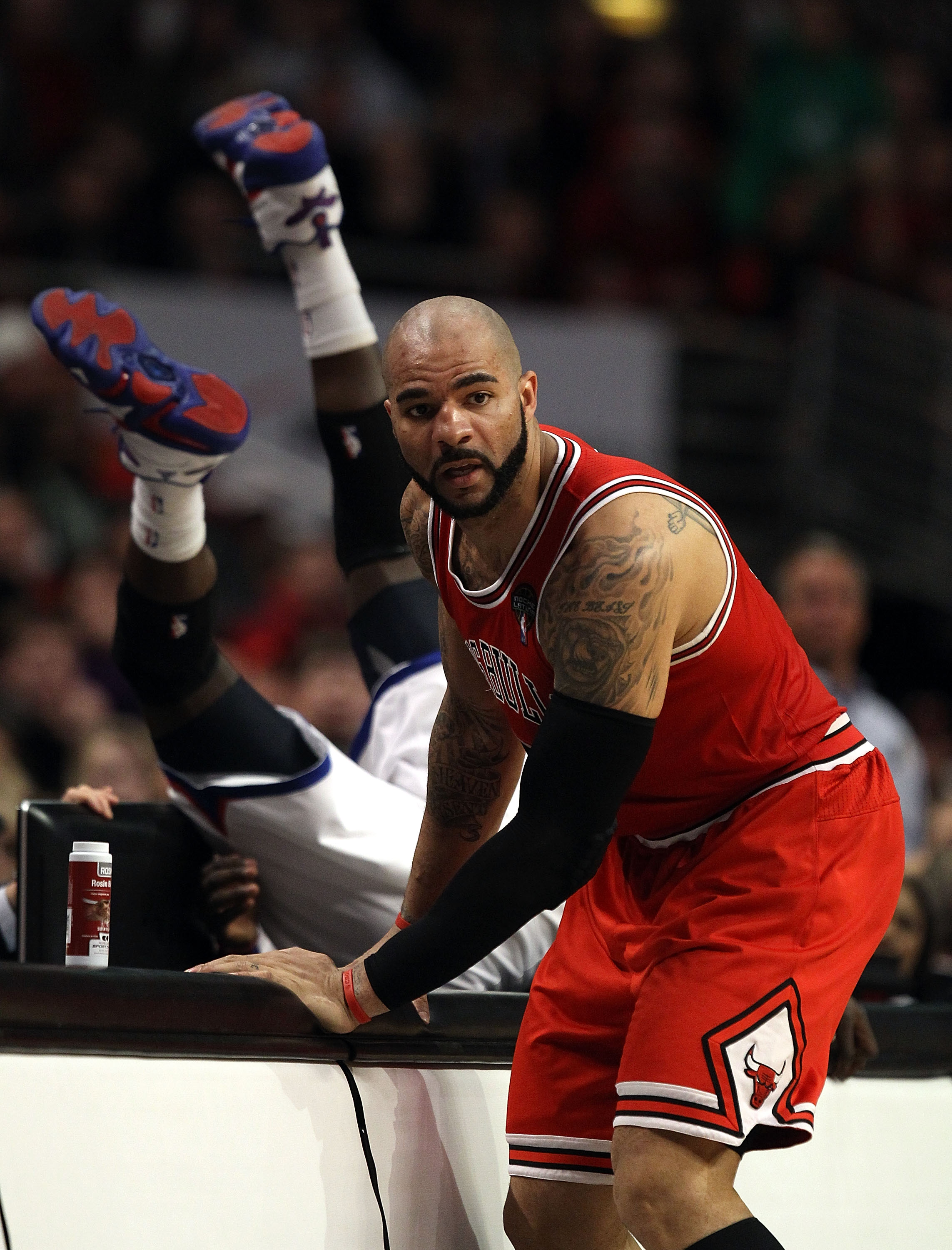 CHICAGO, IL - MARCH 28: Carlos Boozer #5 of the Chicago Bulls stops at the scorer's table as Jrue Holiday #11 of the Philadelphia 76ers flips over the edge at the United Center on March 28, 2011 in Chicago, Illinois. The 76ers defeated the Bulls 97-85. NO