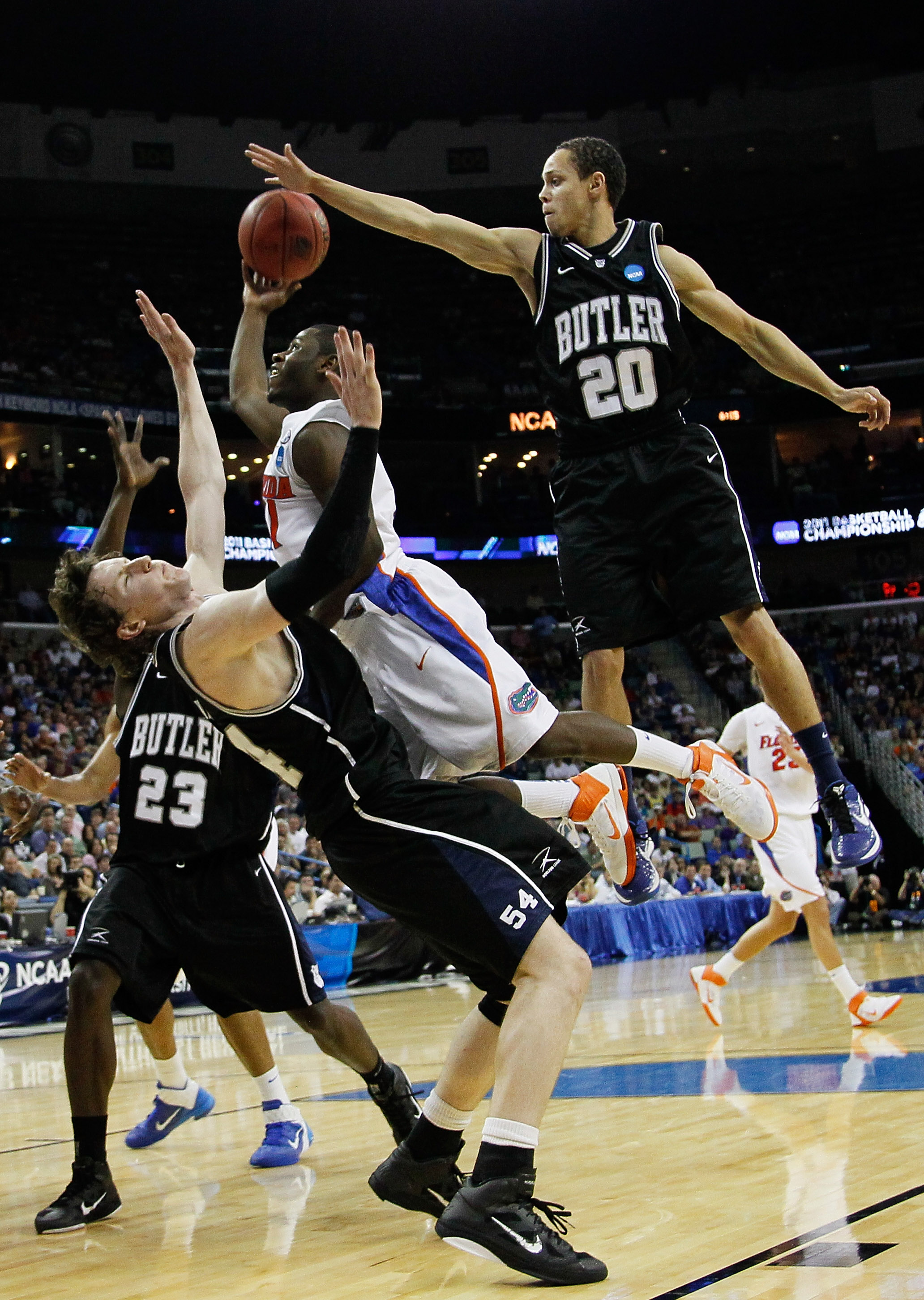 NEW ORLEANS, LA - MARCH 26:  Erving Walker #11 of the Florida Gators fouls Matt Howard #54 as Chrishawn Hopkins #20 of the Butler Bulldogs tries to block his shot in the second half during the Southeast regional final of the 2011 NCAA men's basketball tou
