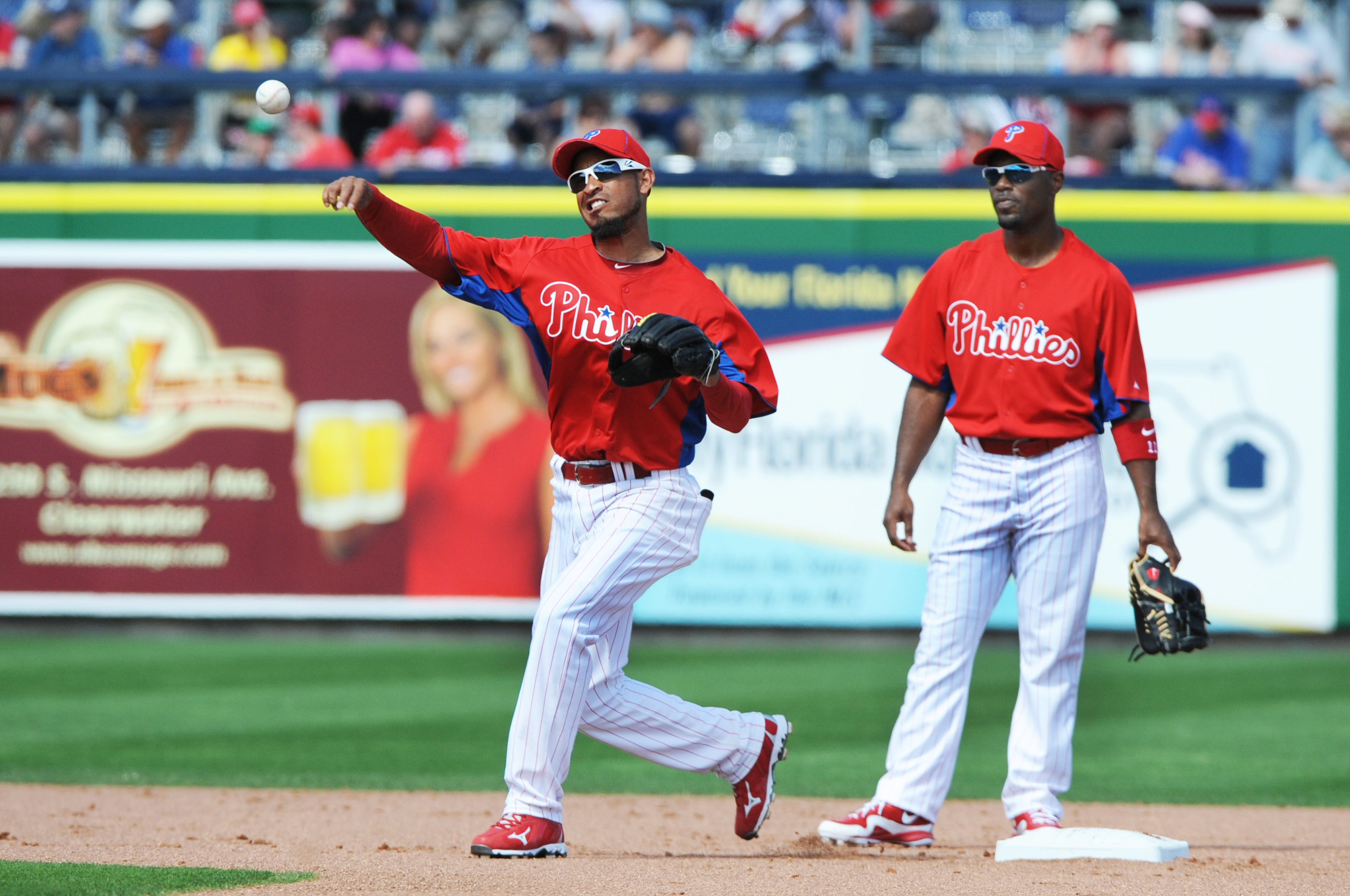 CLEARWATER, FL - FEBRUARY 27:  Infielder Wilson Valdez #21 throws in front of shortstop Jimmy Rollins #11 of the Philadelphia Phillies during play against the New York Yankees February 27, 2011 at Bright House Field in Clearwater, Florida.  (Photo by Al M