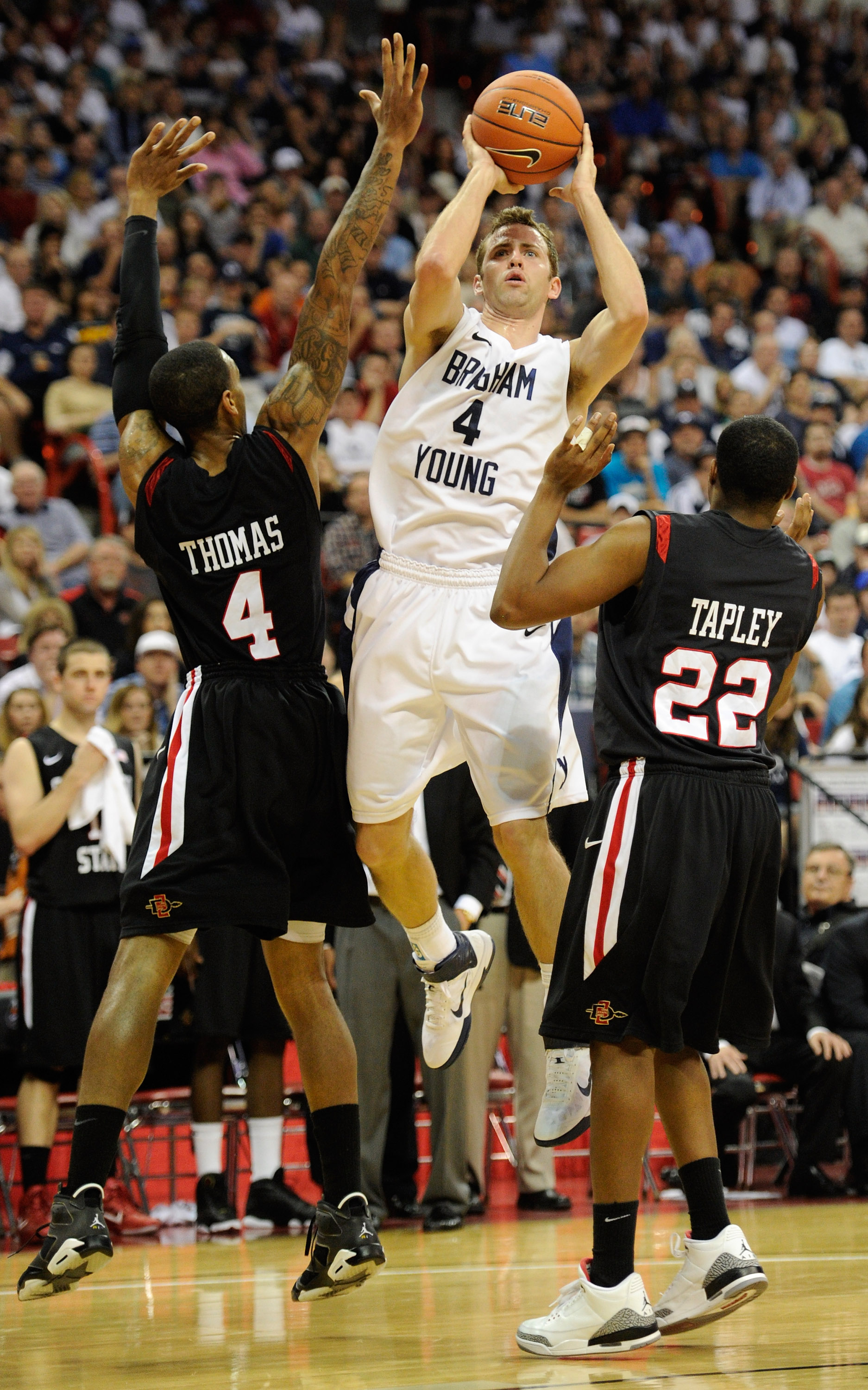 LAS VEGAS, NV - MARCH 12:  Jackson Emery #4 of the Brigham Young University Cougars shoots between Malcolm Thomas #4 and Chase Tapley #22 of the San Diego State Aztecs during the championship game of the Conoco Mountain West Conference Basketball tourname