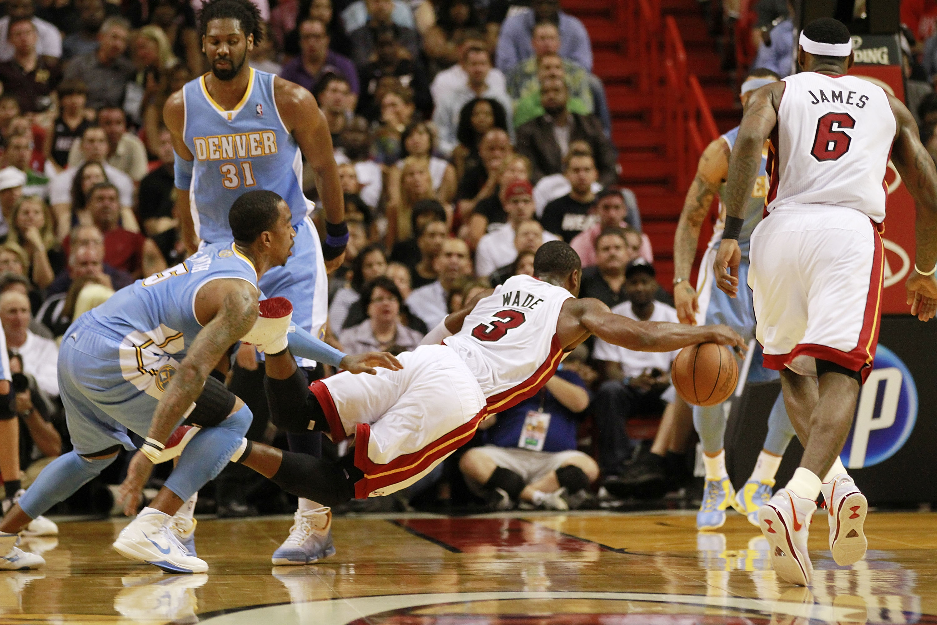 MIAMI, FL - MARCH 19:  Guard Dwyane Wade #3 of the Miami Heat is fouled by guard J.R. Smith (R) of the Denver Nuggets at American Airlines Arena on March 19, 2011 in Miami, Florida. The Heat defeated the Nuggets 103-98. NOTE TO USER: User expressly acknow