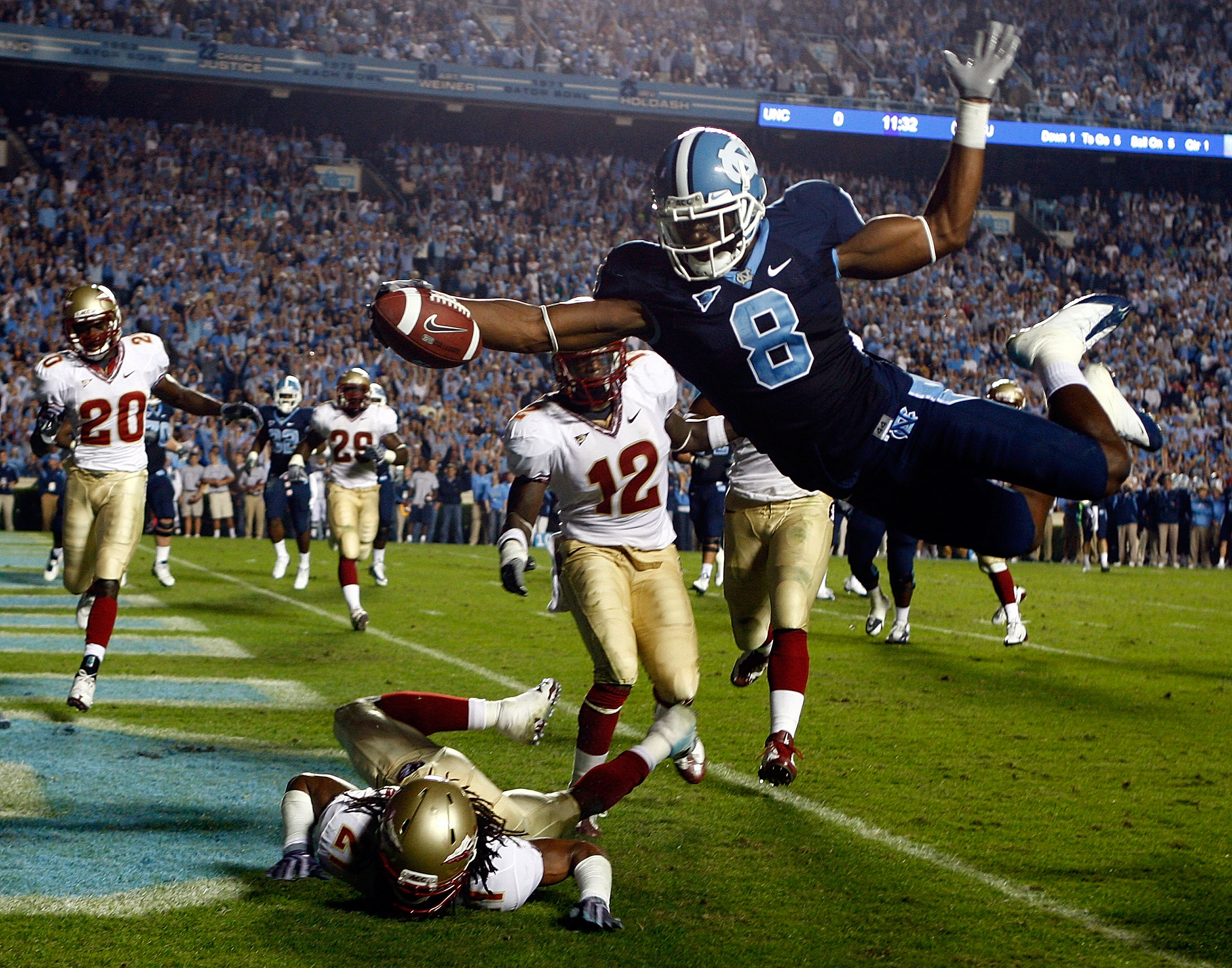 CHAPEL HILL, NC - OCTOBER 22:  Greg Little #8 of the North Carolina Tar Heels dives past Florida State Seminole defenders Patrick Robinson #21 and Nigel Carr #12 for a first quarter touchdown at Kenan Stadium on October 22, 2009 in Chapel Hill, North Caro