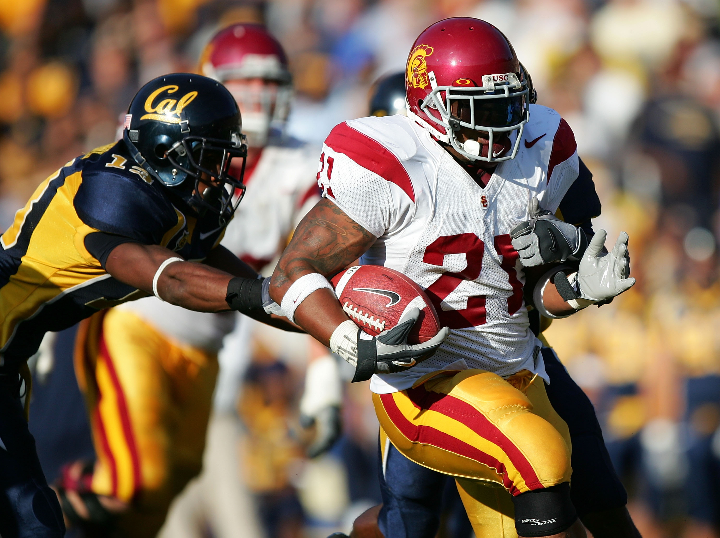 BERKELEY, CA - NOVEMBER 12:  LenDale White #21 of the USC Trojans runs with the ball against Daymeion Hughes #13 of the California Golden Bears at Memorial Stadium on November 12, 2005 in Berkeley, California.  (Photo by Jed Jacobsohn/Getty Images)