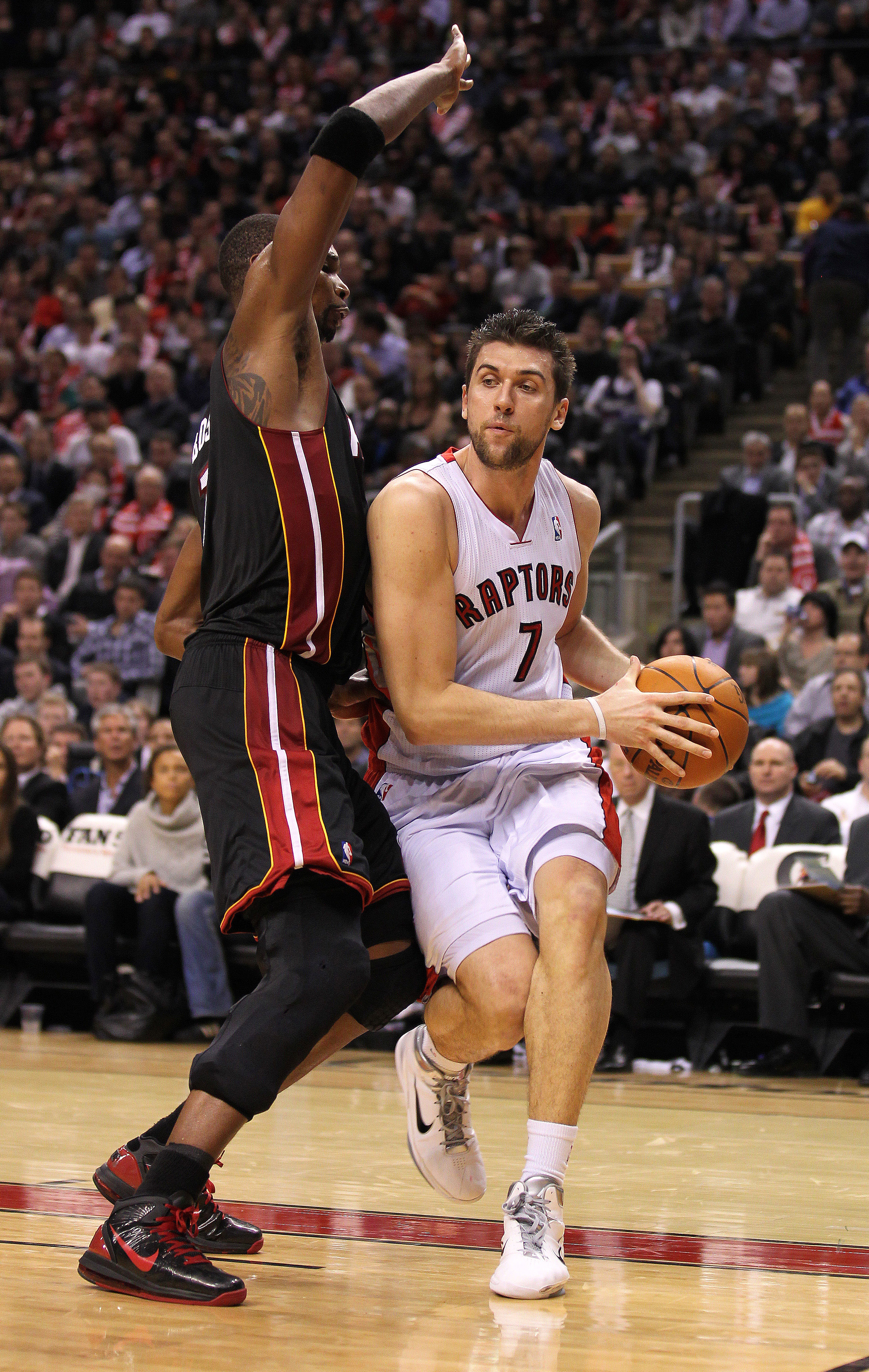 TORONTO, CANADA - FEBRUARY 16:  Chris Bosh #1 of the Miami Heat tries to defend against Andrea Bargnani #7 of the Toronto Raptors in a game on February 16, 2011 at the Air Canada Centre in Toronto, Canada. The Heat defeated the Raptors 103-95. (Photo by C