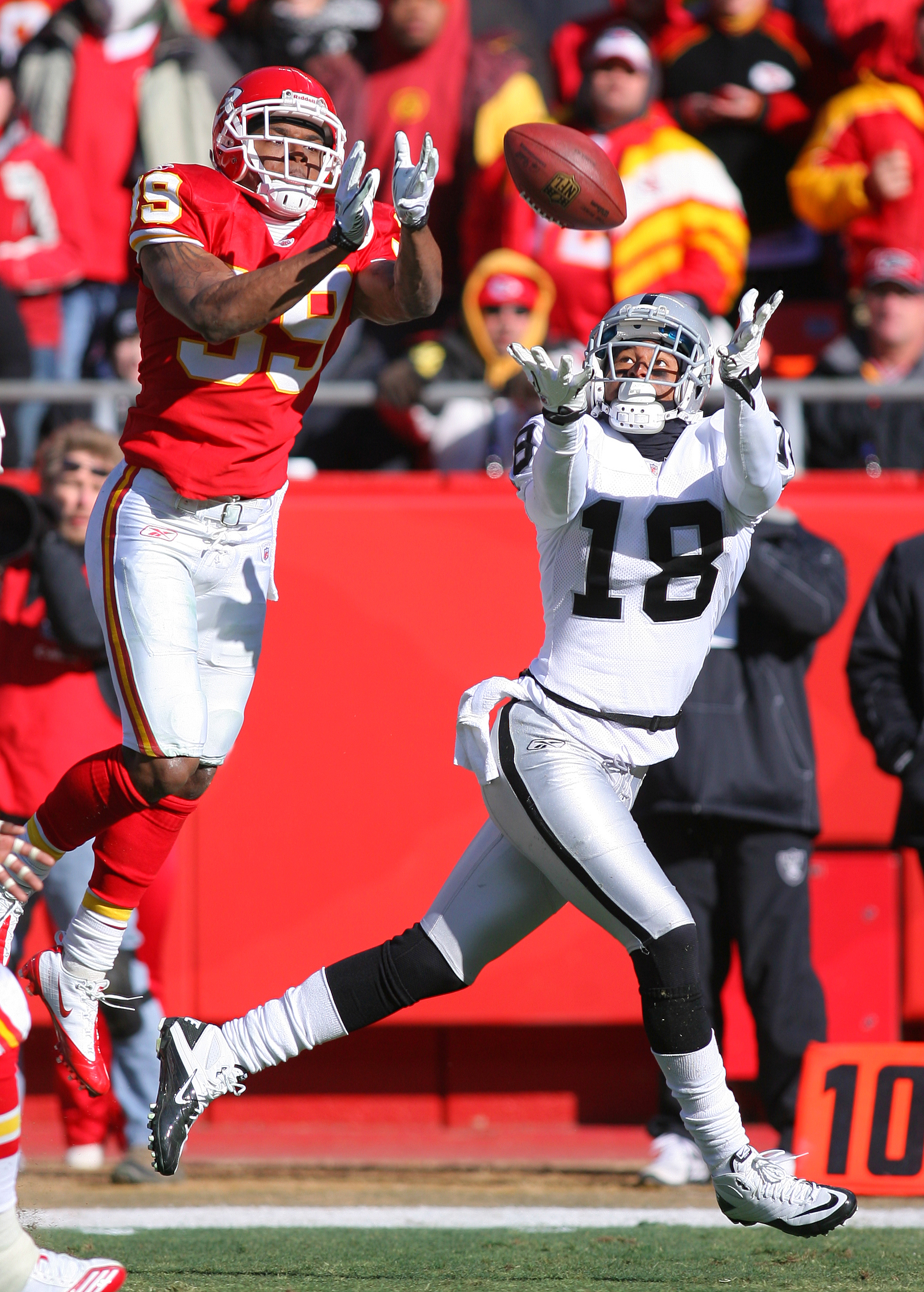 KANSAS CITY, MO - JANUARY 02:  Wide receiver Louis Murphy #18 of the Oakland Raiders catches a pass while defended by cornerback Brandon Carr #39 of the Kansas City Chiefs in a game at Arrowhead Stadium on January 2, 2011 in Kansas City, Missouri.  (Photo
