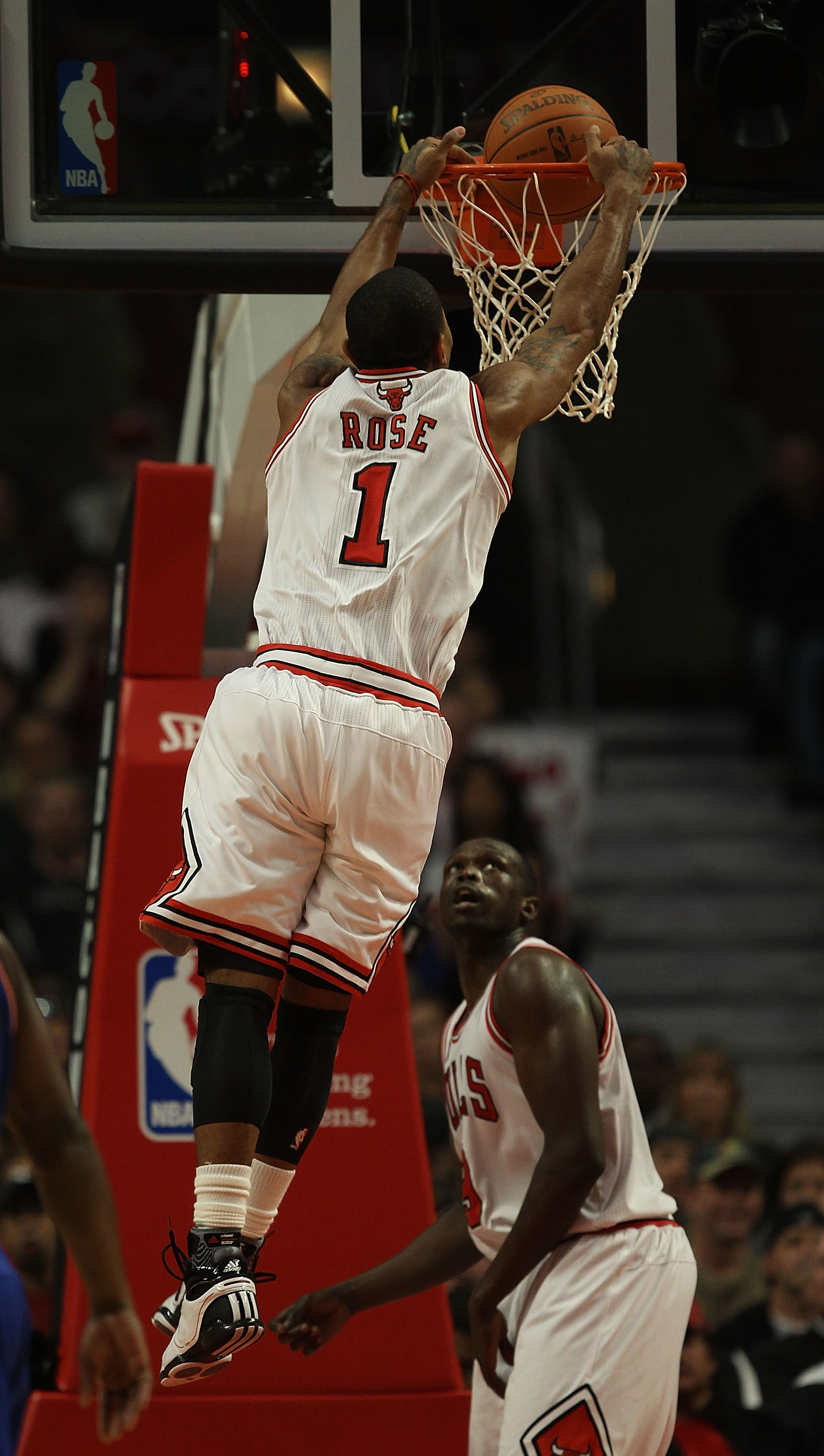CHICAGO - NOVEMBER 04: Loul Deng #9 of the Chicago Bulls watches as his teammate Derrick Rose #1 dunks the ball against the New York Knicks at the United Center on November 4, 2010 in Chicago, Illinois. NOTE TO USER: User expressly acknowledges and agrees