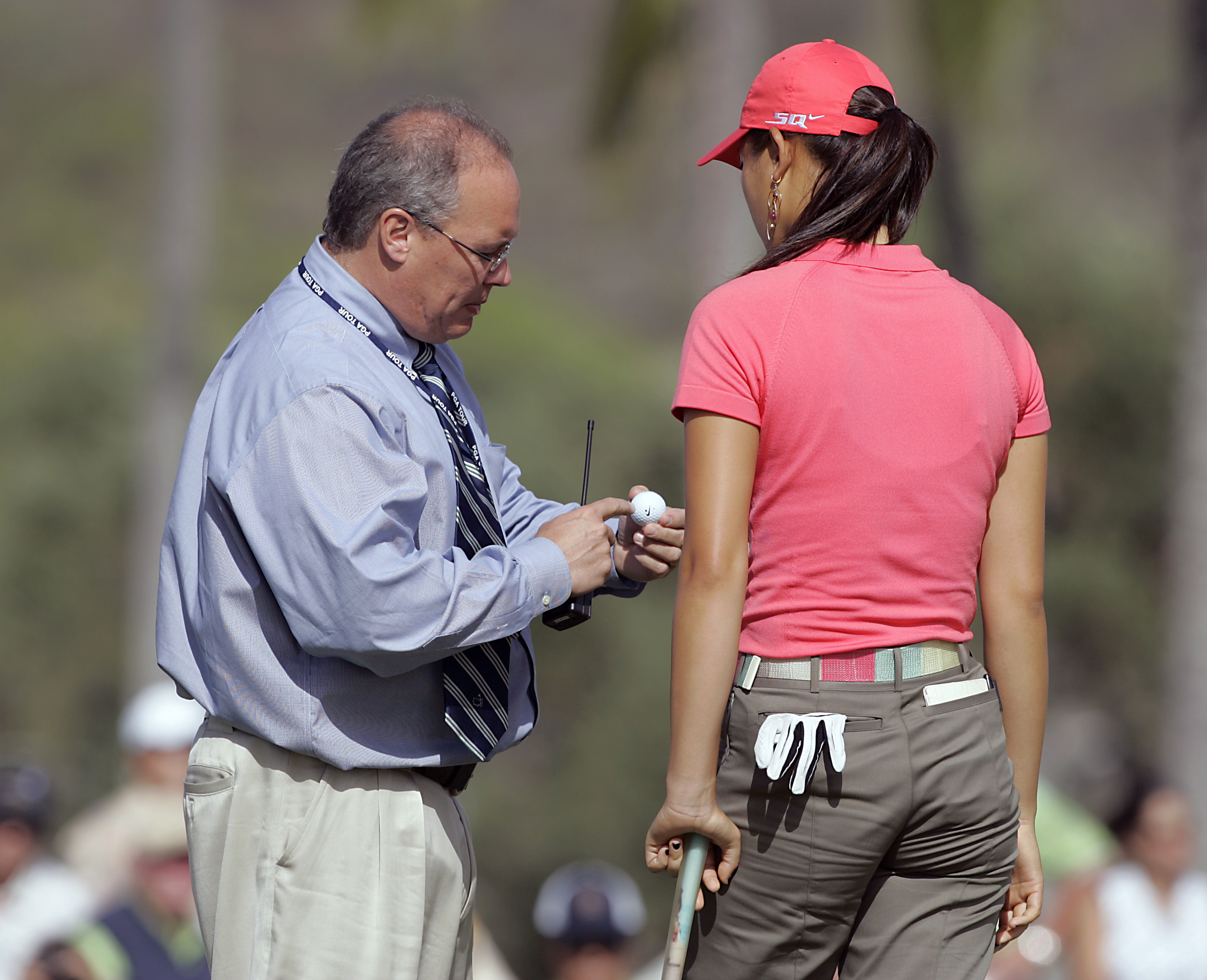UNITED STATES - JANUARY 12:  PGA TOUR Rules official John Mutch, left, examines Michelle Wie's ball for scuff marks on the 17th green during the first round of the PGA TOUR's Sony Open, January 12, 2006 at the Waialae Country Club in Honolulu, Hawaii.  (P