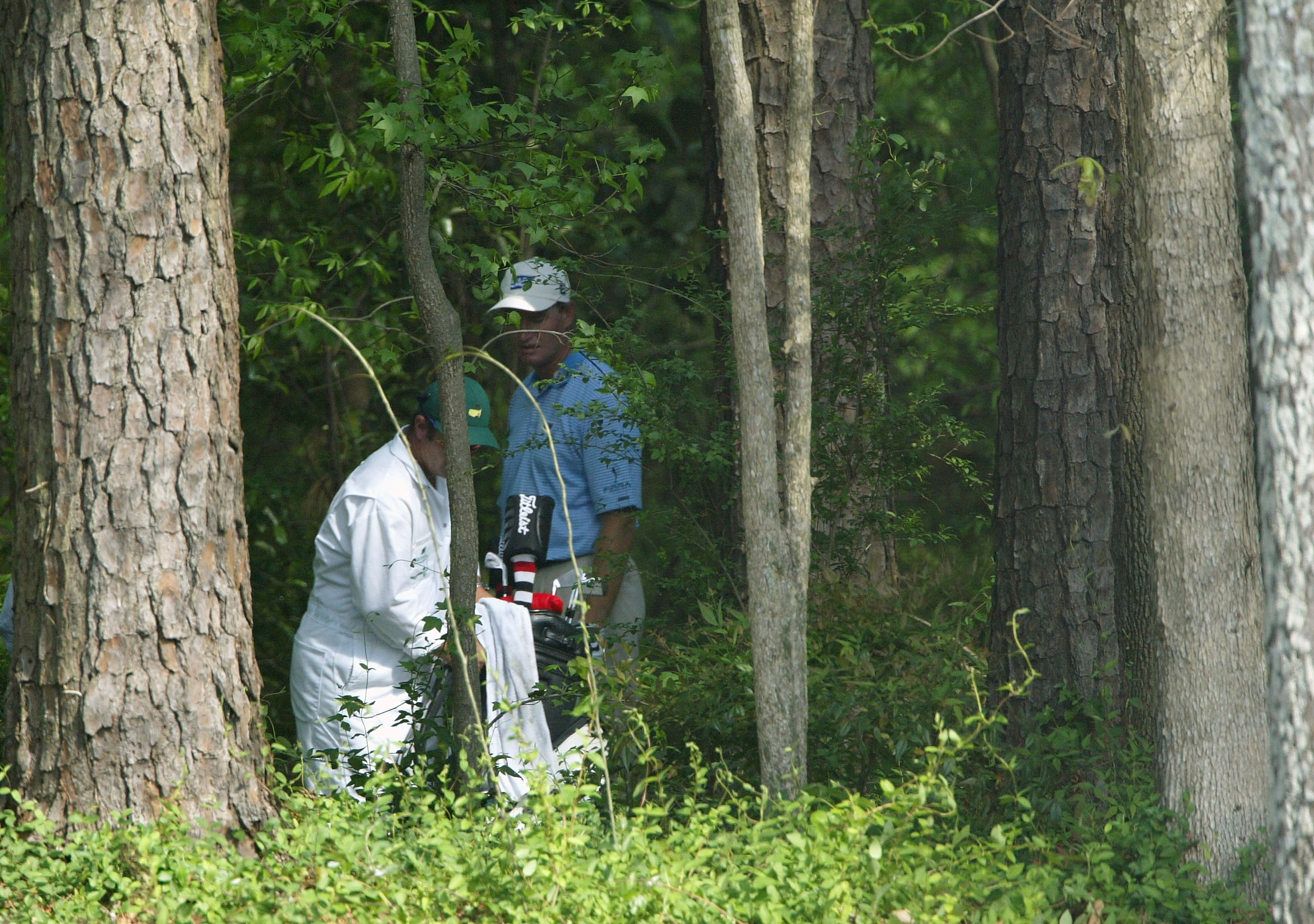 AUGUSTA, GA - APRIL 10:  Ernie Els of South Africa along with his caddie Ricci Roberts look over a shot from the trees on the 11th hole during the third round of the Masters at the Augusta National Golf Club on April 10, 2004 in Augusta, Georgia.  (Photo