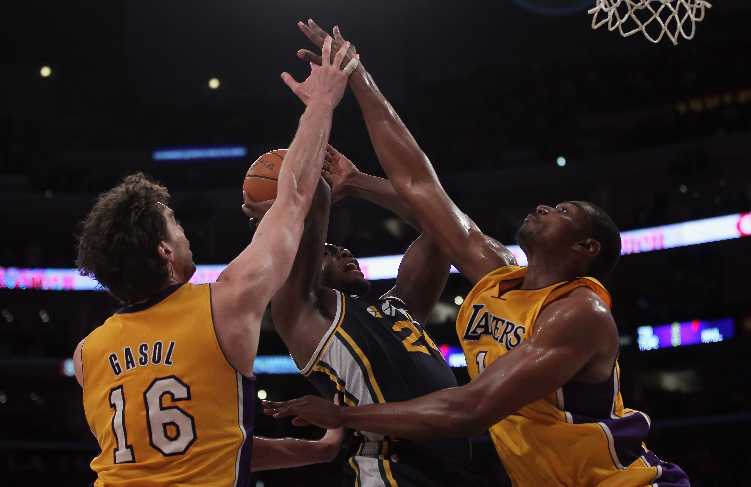 LOS ANGELES, CA - JANUARY 25:   Pau Gasol (L) #16 and Andrew Bynum (R) #17 the Los Angeles Lakers tie up Paul Millsap (center) #24 of the Utah Jazz in the first half at Staples Center on January 25, 2011 in Los Angeles, California. NOTE TO USER: User expr