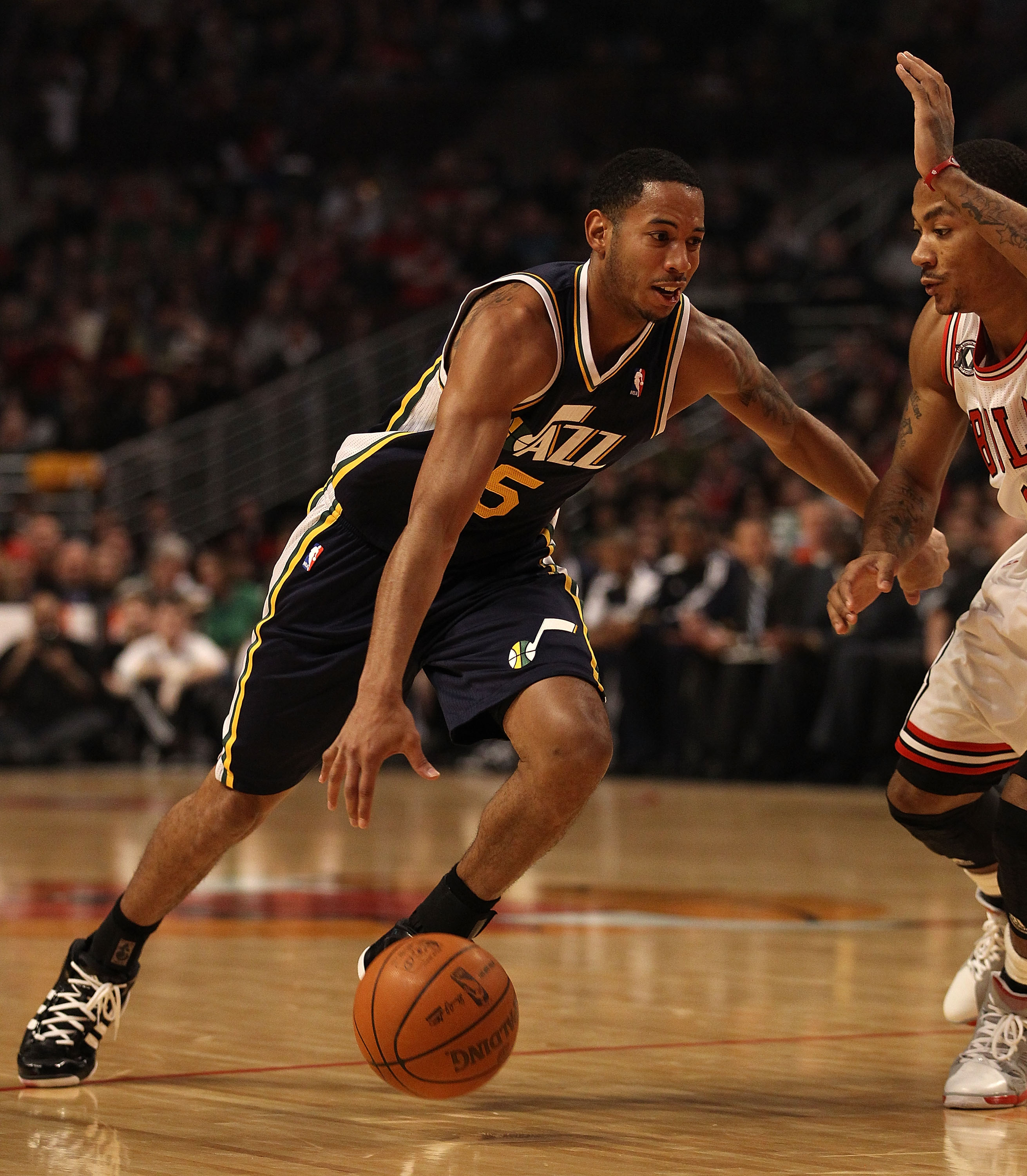 CHICAGO, IL - MARCH 12: Devin Harris #5 of the Utah Jazz drives against Derrick Rose #1 of the Chicago Bulls at the United Center on March 12, 2011 in Chicago, Illinois. The Bulls defeated the Jazz 118-100. NOTE TO USER: User expressly acknowledges and ag
