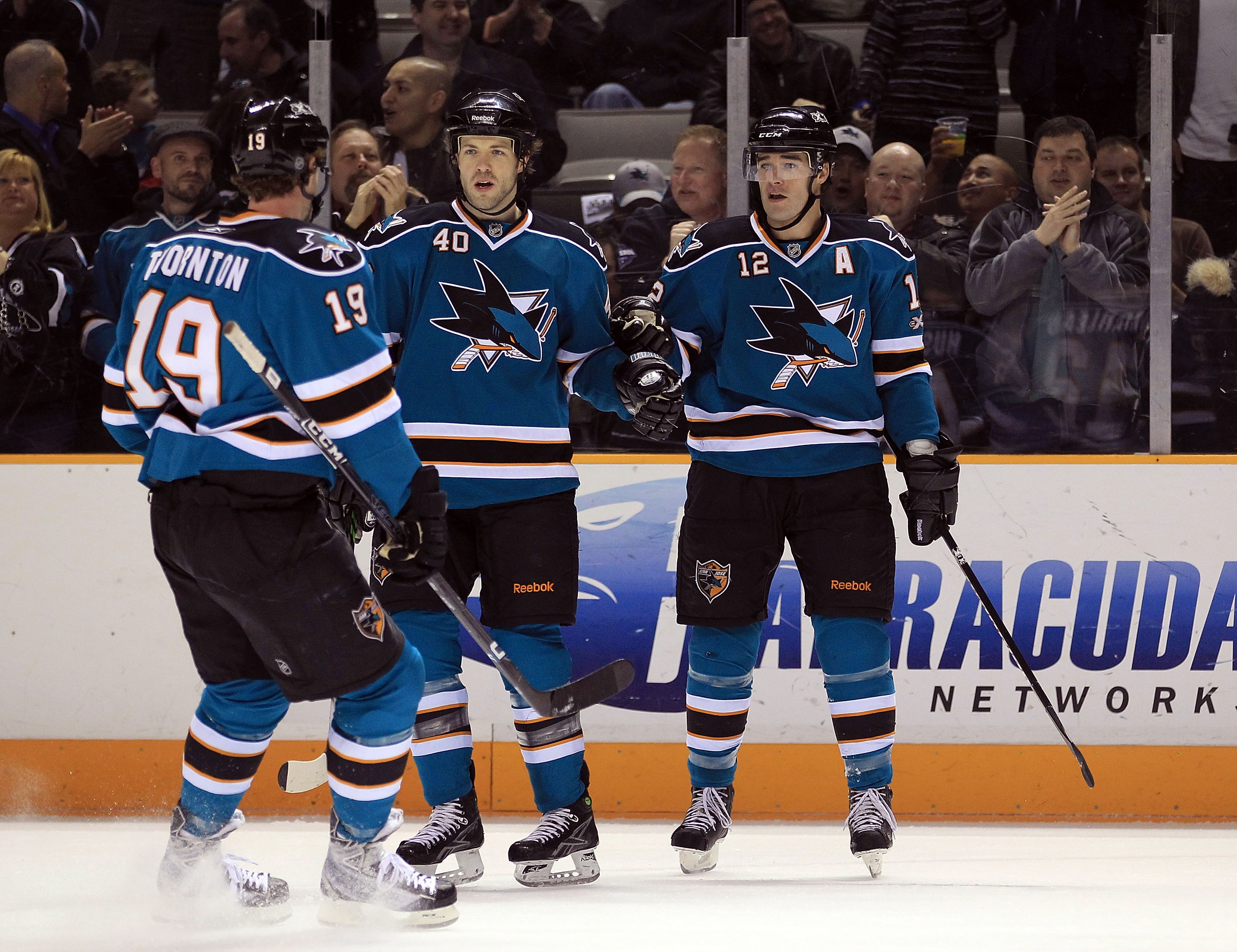SAN JOSE, CA - JANUARY 11:  Patrick Marleau #12 is congratulated by Kent Huskins #40 and Joe Thornton #19 of the San Jose Sharks after Marleau scored a goal against the Toronto Maple Leafs at HP Pavilion on January 11, 2011 in San Jose, California.  (Phot