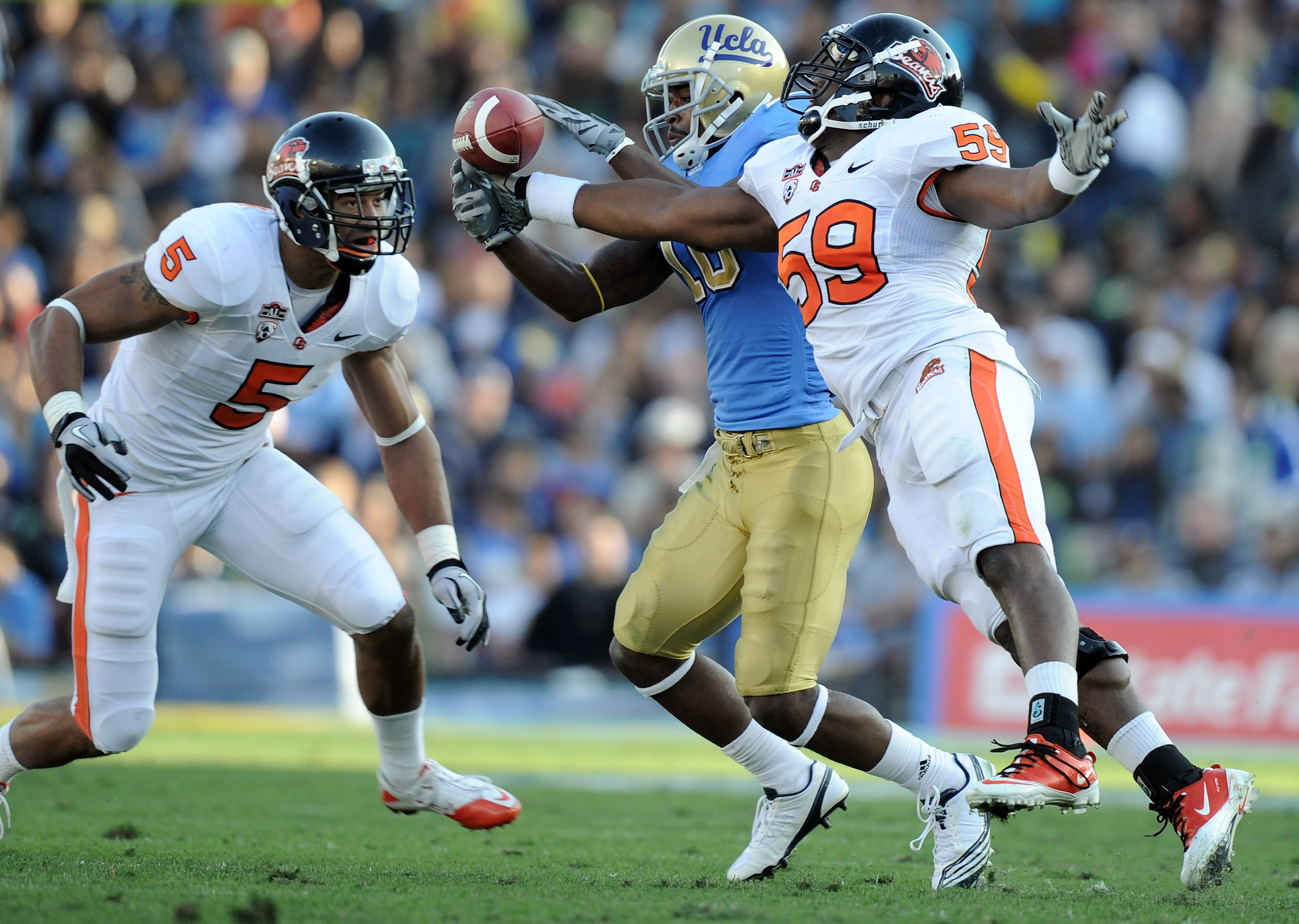 PASADENA, CA - NOVEMBER 06:  Akeem Ayers #10 of the UCLA Bruins makes a catch in front of Dwight Roberson #59 and Cameron Collins #5 of the Oregon State Beavers at the Rose Bowl on November 6, 2010 in Pasadena, California.  (Photo by Harry How/Getty Image