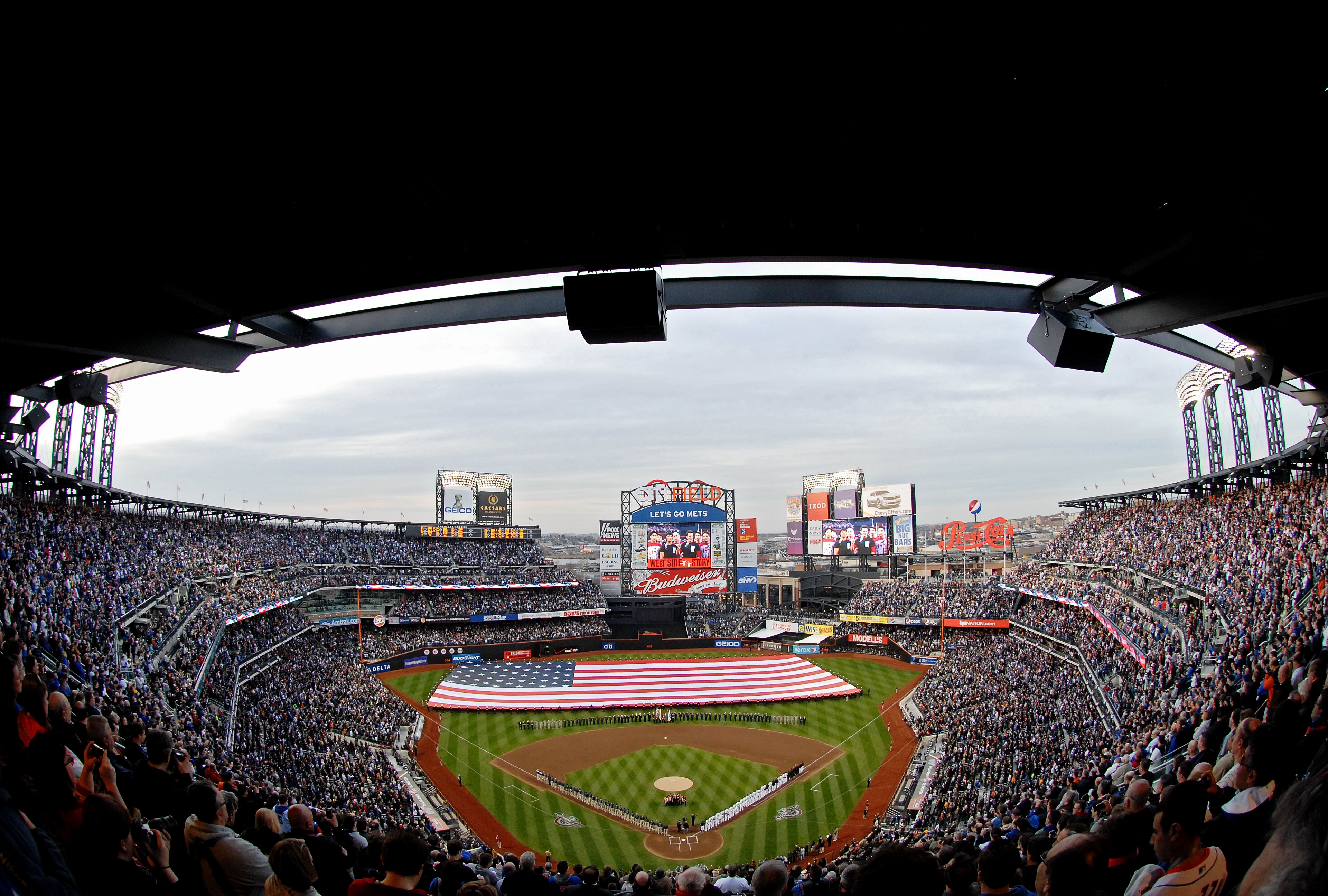 NEW YORK - APRIL 13: Members of the U.S. military hold a giant flag on the field as the National Anthem is performed prior to the start of the opening day game between the San Diego Padres and the New York Mets at Citi Field on April 13, 2009 in the Flush