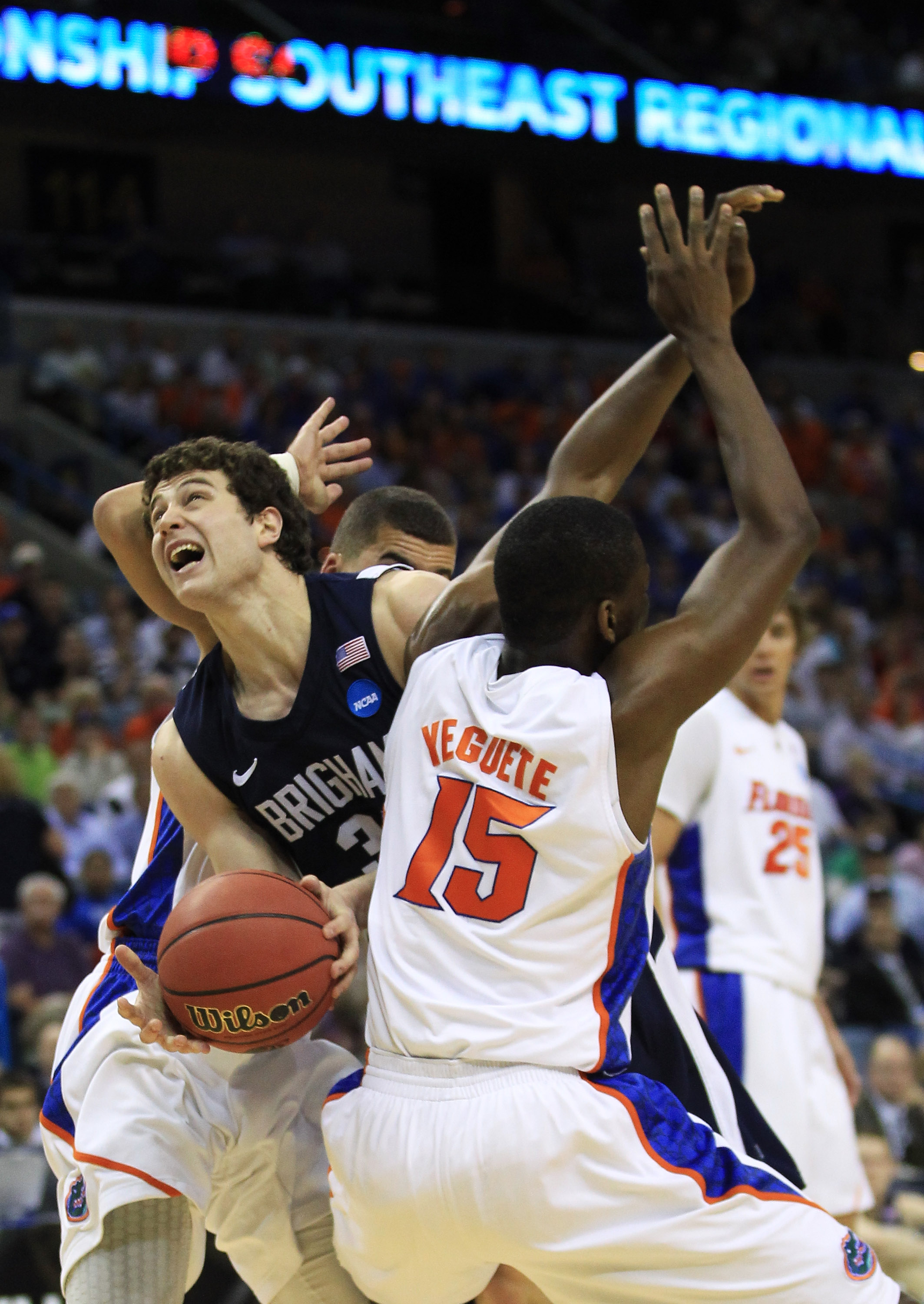 NEW ORLEANS, LA - MARCH 24:  Jimmer Fredette #32 of the Brigham Young Cougars is blocked Brigham Young Cougars Scottie Wilbekin #5 and Will Yeguete #15 of the Florida Gators in the second half during the Southeast regional of the 2011 NCAA men's basketbal