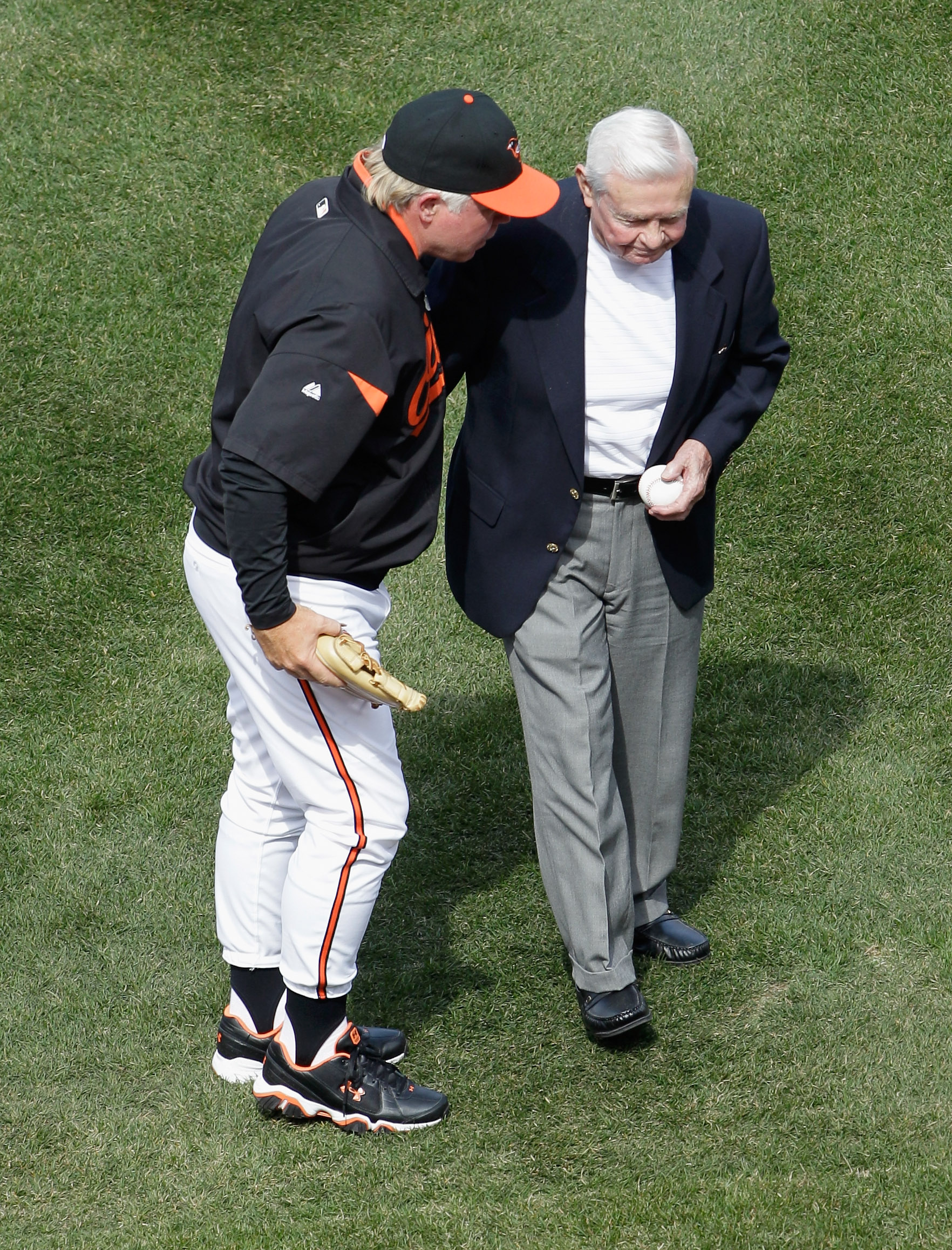 BALTIMORE, MD - APRIL 04: Buck Showalter #26 manager of the Baltimore Orioles talks with former Orioles manager Earl Weaver (R) after Weaver threw out the ceremonial first pitch before the start of their game against the Detroit Tigers  during opening day