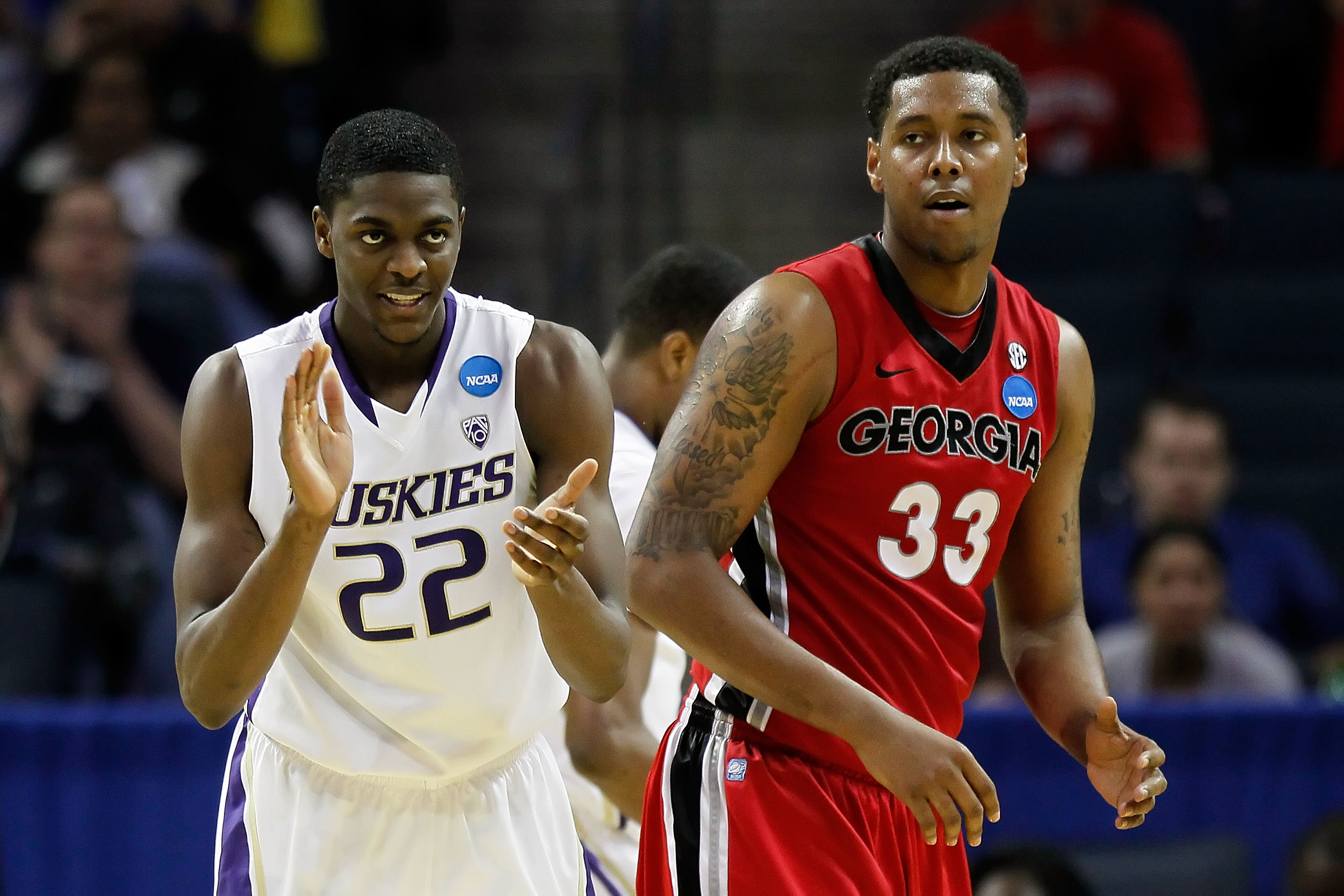 CHARLOTTE, NC - MARCH 18:  Justin Holiday #22 of the Washington Huskies reacts alongside Trey Thompkins #33 of the Georgia Bulldogs in the second half during the second round of the 2011 NCAA men's basketball tournament at Time Warner Cable Arena on March