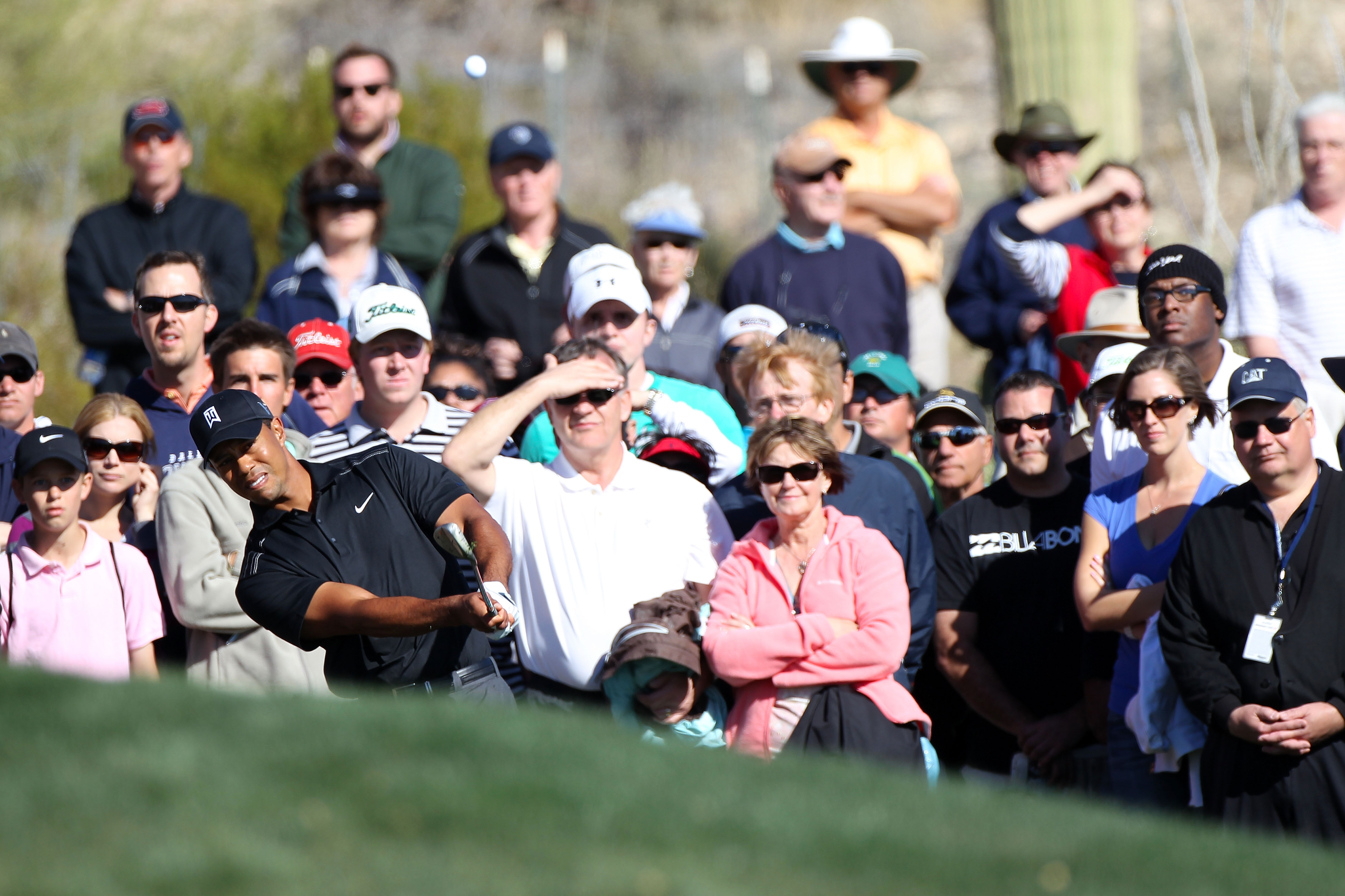 MARANA, AZ - FEBRUARY 23:  Tiger Woods hits an approach shot on the 15th hole as a gallery of fans looks on during the first round of the Accenture Match Play Championship at the Ritz-Carlton Golf Club on February 23, 2011 in Marana, Arizona.  (Photo by S