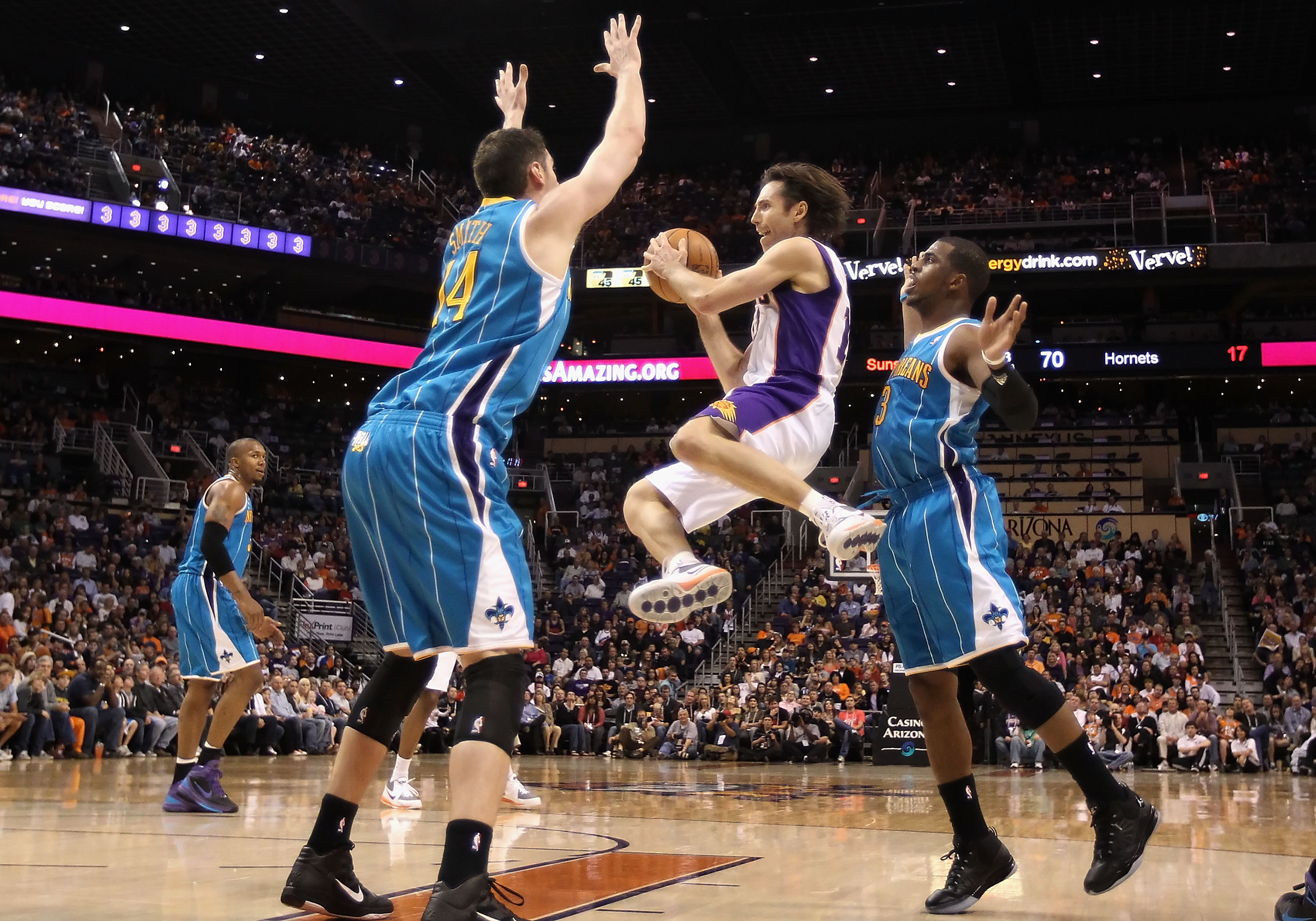 PHOENIX, AZ - JANUARY 30:  Steve Nash #13 of the Phoenix Suns makes a leaping pass guarded by Jason Smith #14 and Chris Paul #3 of the New Orleans Hornets during the NBA game at US Airways Center on January 30, 2011 in Phoenix, Arizona. The Suns defeated