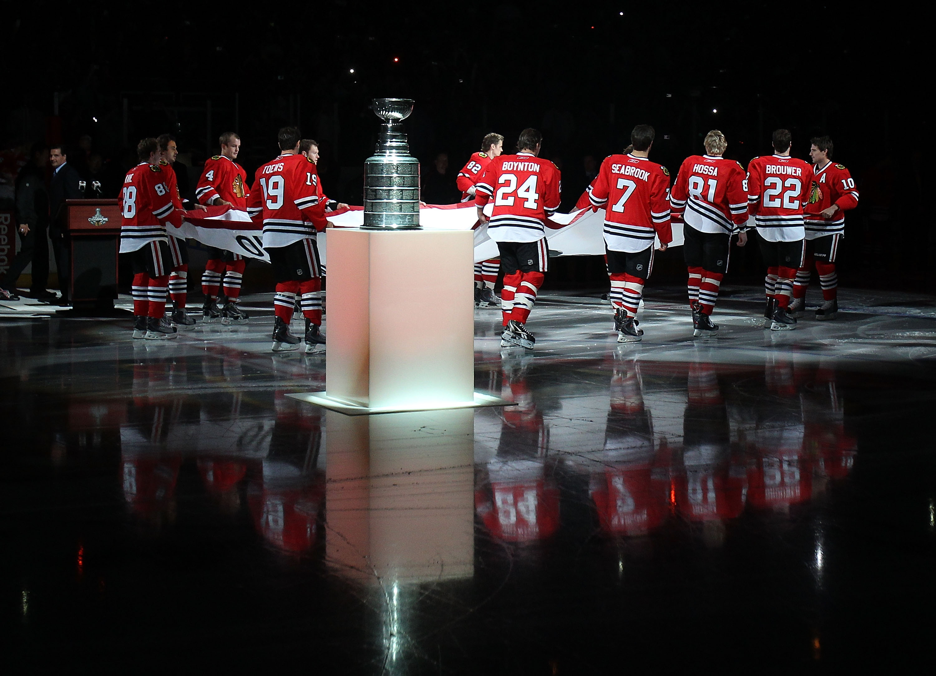 CHICAGO - OCTOBER 09: Members of the Chicago Blackhawks carry the Stanley Cup Championship banner across the ice past the Stanley Cup in a ceremony before the Blackhawks season home opening game against the Detroit Red Wings at the United Center on Octobe
