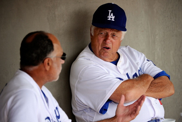 GLENDALE, AZ - MARCH 15:  Hall of Fame manager Tommy Lasorda #2 of the Los Angeles Dodgers speaks to first base coach Davey Lopes in the dugout prior to the start of the spring training baseball game against the Texas Rangers at Camelback Ranch on March 1