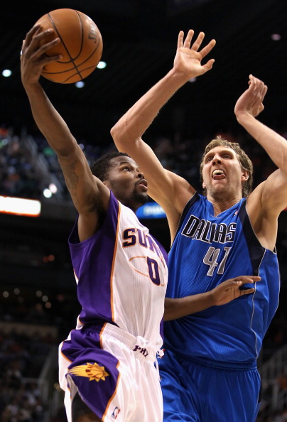PHOENIX, AZ - MARCH 27:  Aaron Brooks #0 of the Phoenix Suns lays up a shot past Dirk Nowitzki #41 of the Dallas Mavericks during the NBA game at US Airways Center on March 27, 2011 in Phoenix, Arizona. The Mavericks defeated the Suns 91-83. NOTE TO USER: