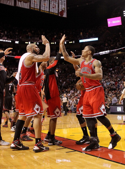 MIAMI, FL - MARCH 06:  Derrick Rose #1 and Carlos Boozer #5 of the Chicago Bulls high five after winning a game against the Miami Heat at American Airlines Arena on March 6, 2011 in Miami, Florida. NOTE TO USER: User expressly acknowledges and agrees that