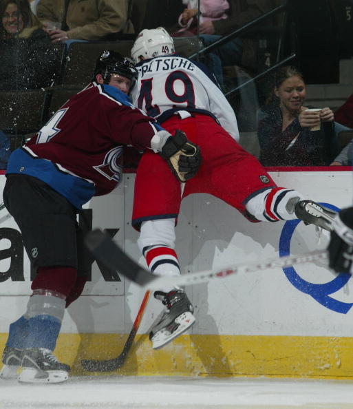 DENVER - DECEMBER 5: John-Michael Liles #4 of the Colorado Avalanche gets hit by Dan Fritsche #49 of the Columbus Blue Jackets on December 5, 2006 at the Pepsi Center in Denver, Colorado. The Blue Jackets shut out the Avalanche 3-0.  (Photo by Bruce Benne