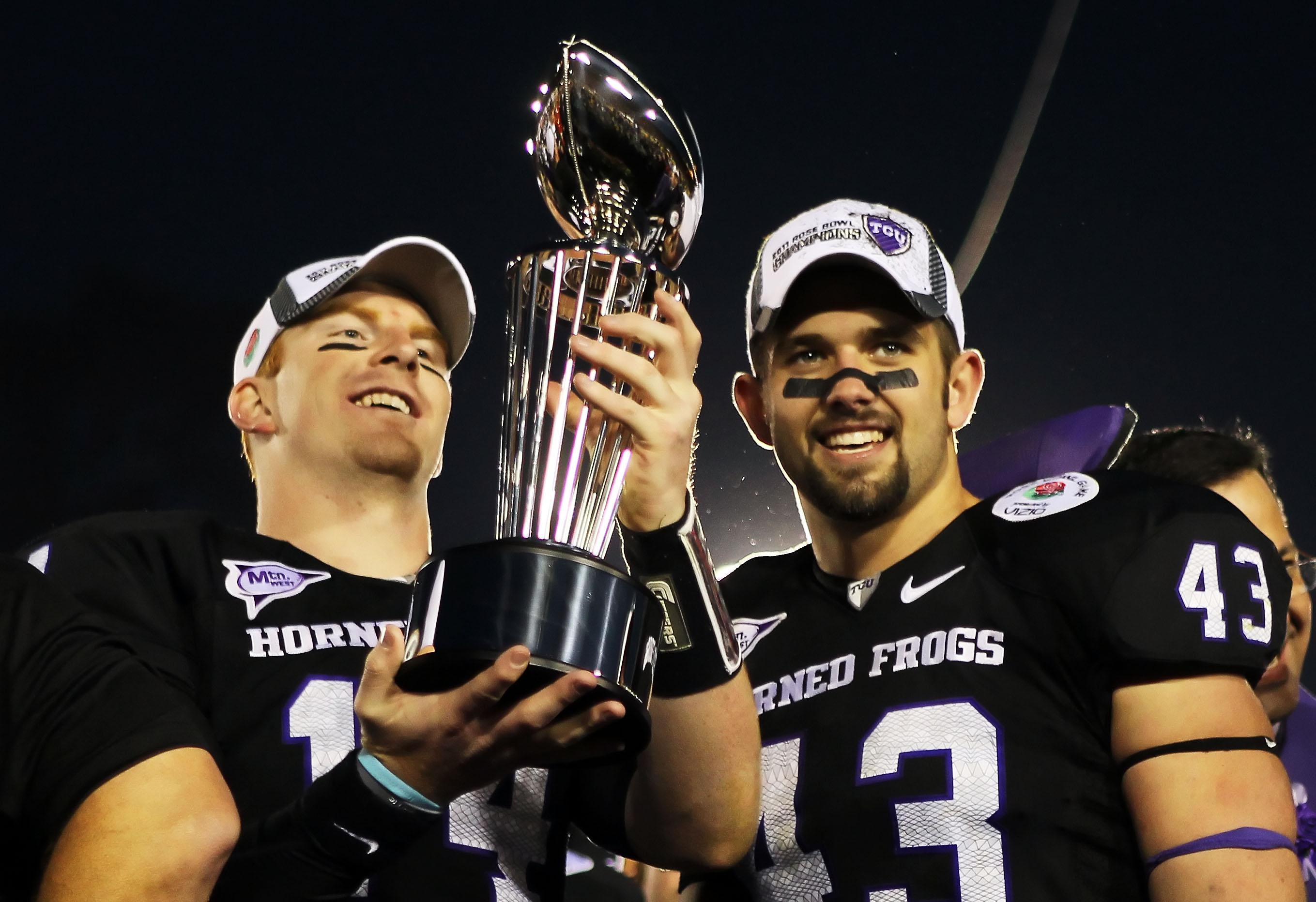 PASADENA, CA - JANUARY 01:  Quarterback Andy Dalton #14 and linebacker Tank Carder #43 of the TCU Horned Frogs hold the Rose Bowl Championship Trophy after defeating the Wisconsin Badgers 21-19 in the 97th Rose Bowl game on January 1, 2011 in Pasadena, Ca