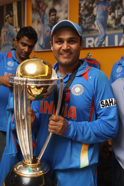 MUMBAI, INDIA - APRIL 02:  Virender Sehwag of India poses with the World Cup trophy in the players dressing room after his side's six wicket victory in the 2011 ICC World Cup Final between India and Sri Lanka at Wankhede Stadium on April 2, 2011 in Mumbai